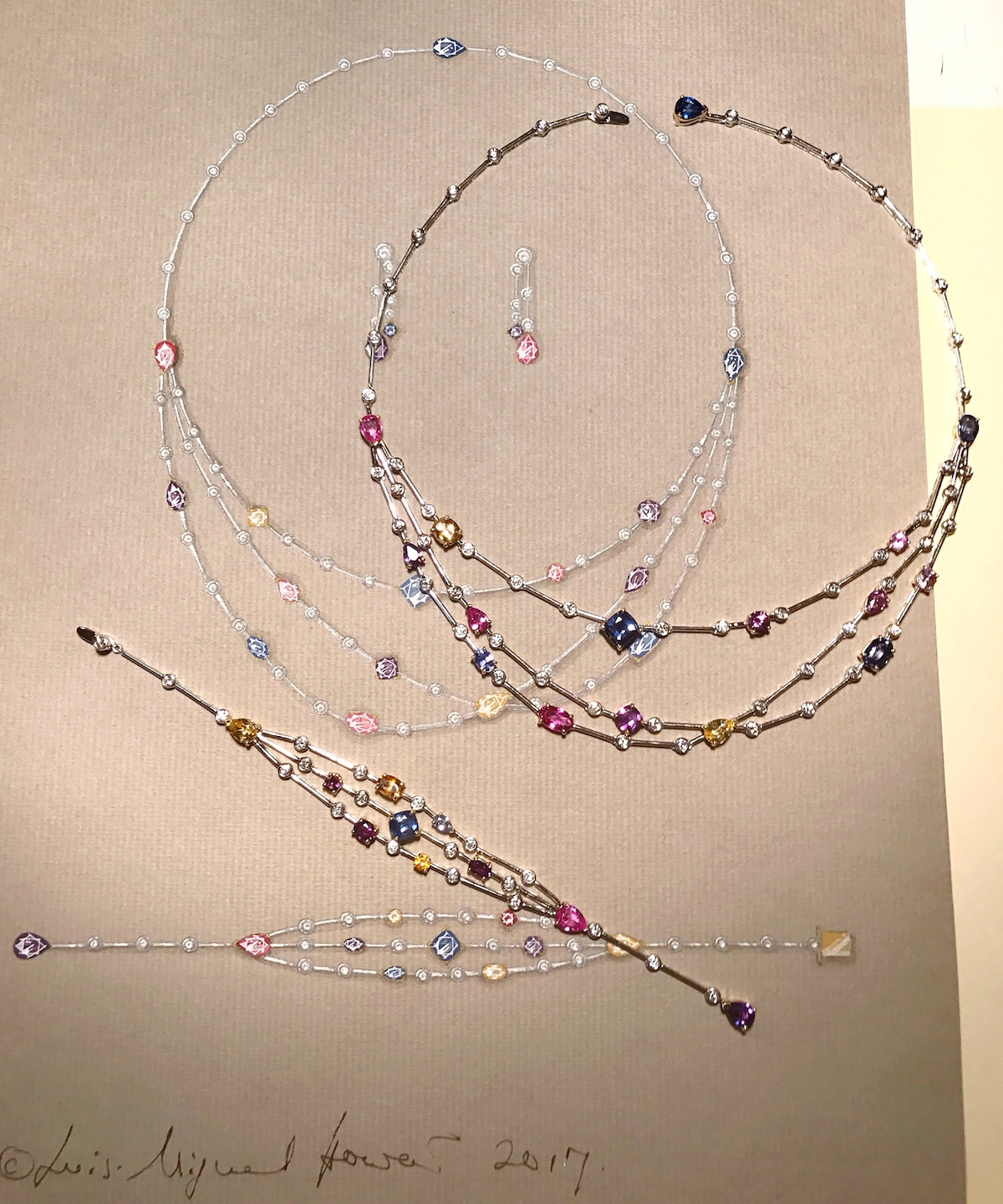 The multi colour sapphire and diamond bracelet and earrings shown next to their original drawings.