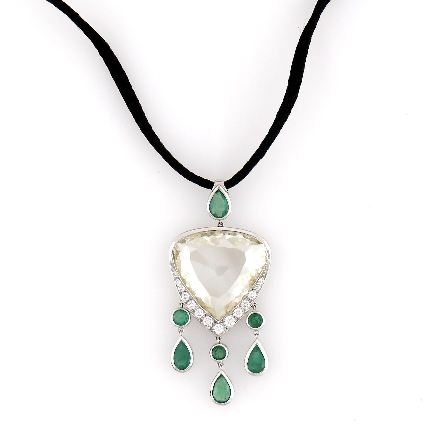 An Indian table diamond set in white gold with emeralds and brilliant cut diamonds.