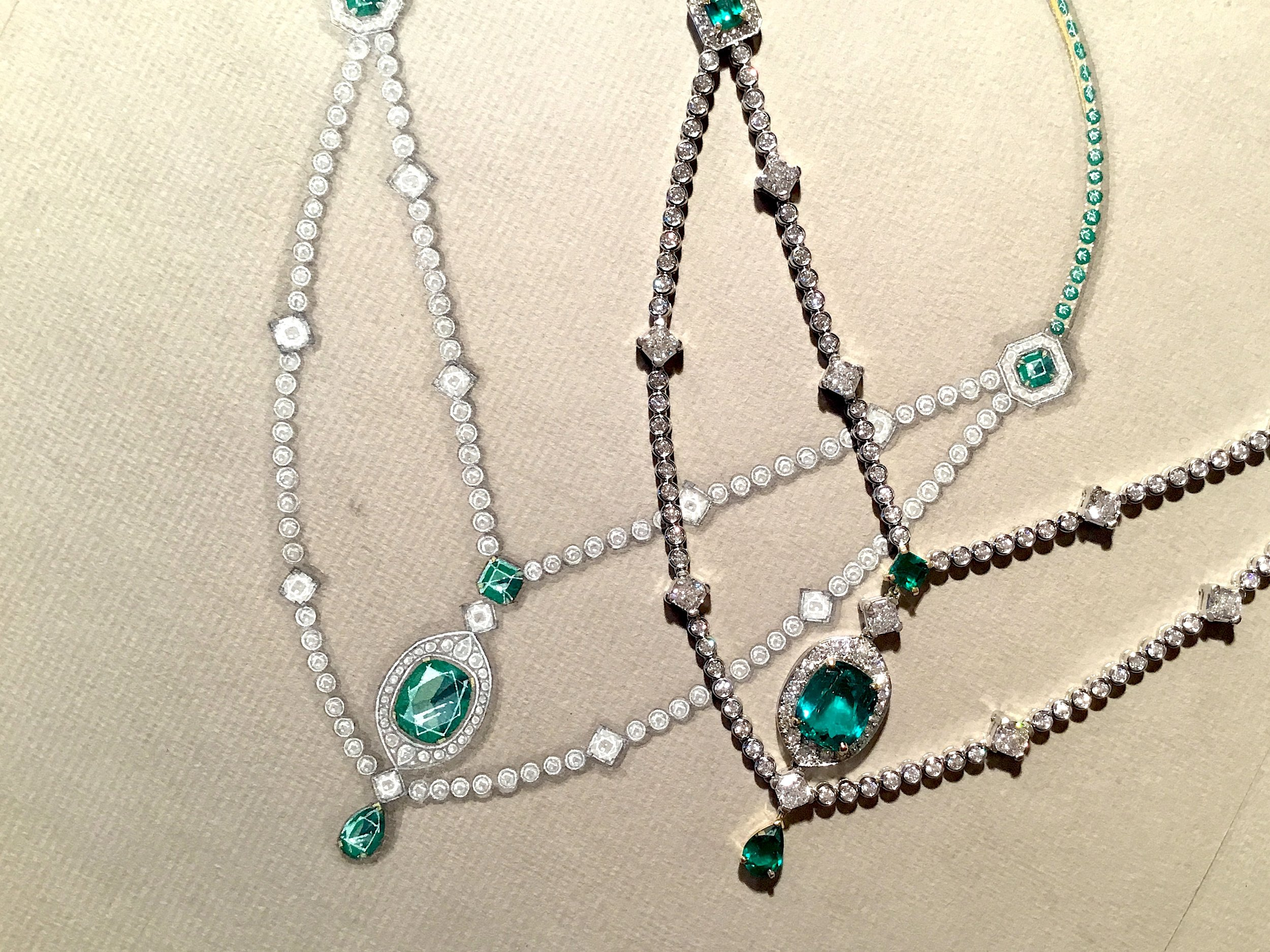 An emerald and diamond necklace, pictured next to the original working drawing.
