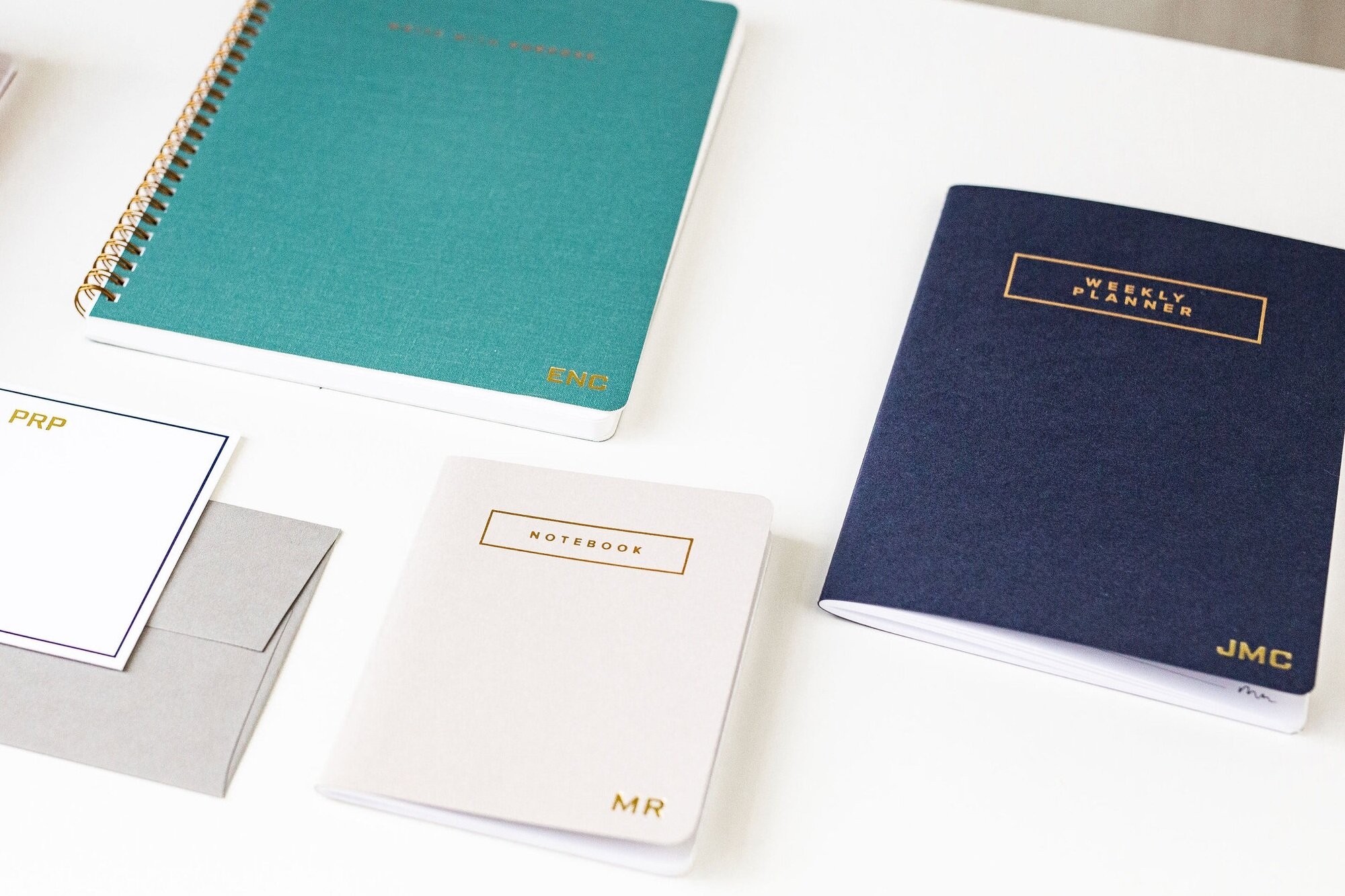 Examples of Marie Mae's items that can include a personal touch. Featuring our social stationery set ($16), the 'write with purpose' notebook in Steel Blue ($28), the small notebook in Cobblestone ($8), and the weekly planner in Navy ($14).