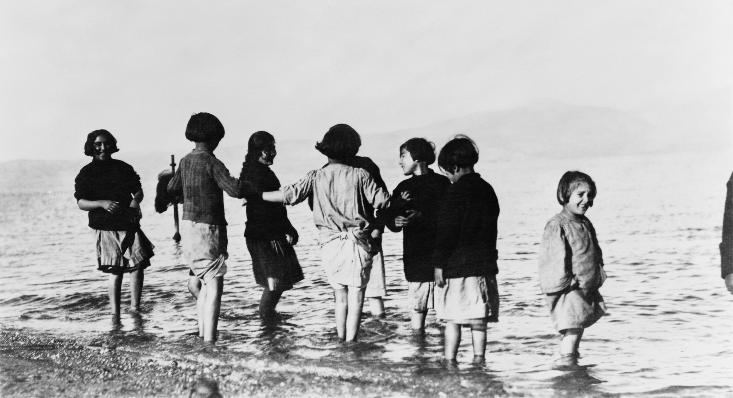 Greek and Armenian refugee children in the sea near Marathon, Greece after their departure from Turkey. The children -- all orphans -- had never seen the sea before. Photo licensed through Wikimedia Commons.