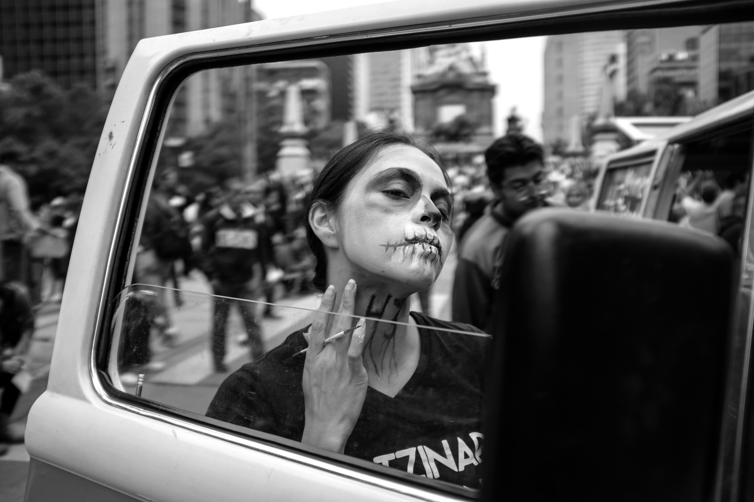 "A protestor paints ""43"" on her neck during a demonstration in Mexico City, Mexico to demand the return of teaching students abducted while on a bus last year. PHOTO CREDIT: MEGHAN DHALIWAL."