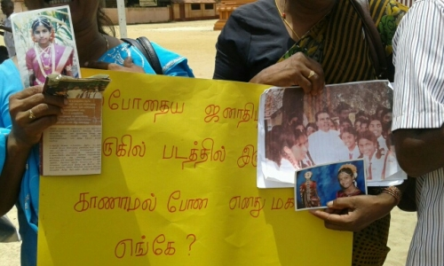 "at a july demonstration in jaffna, a tamil Mother holds photographs of missing daughter alongside a sign reads, ""Where is my missing daughter who is in this photograph next to the current president."" image by Tamilwin, courtesy of tamil guardian."