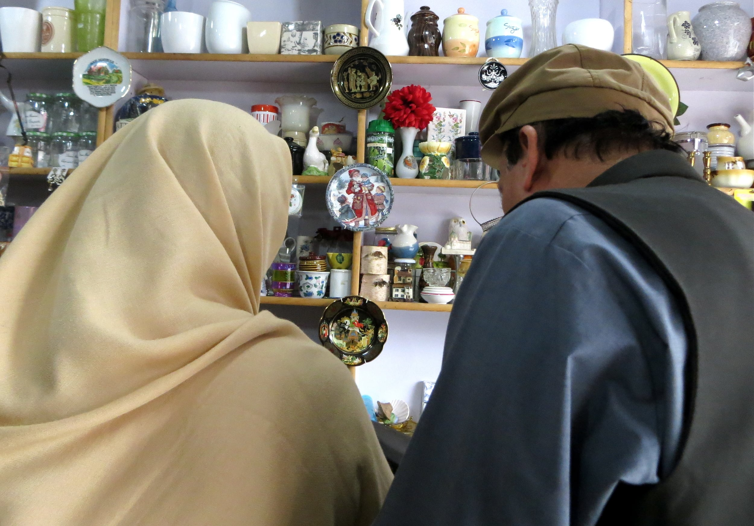 A COUPLE LOOKS AT ITEMS FOR SALE IN A CURIO SHOP IN ISLAMABAD, PAKISTAN. PHOTO BY BEENISH AHMED.