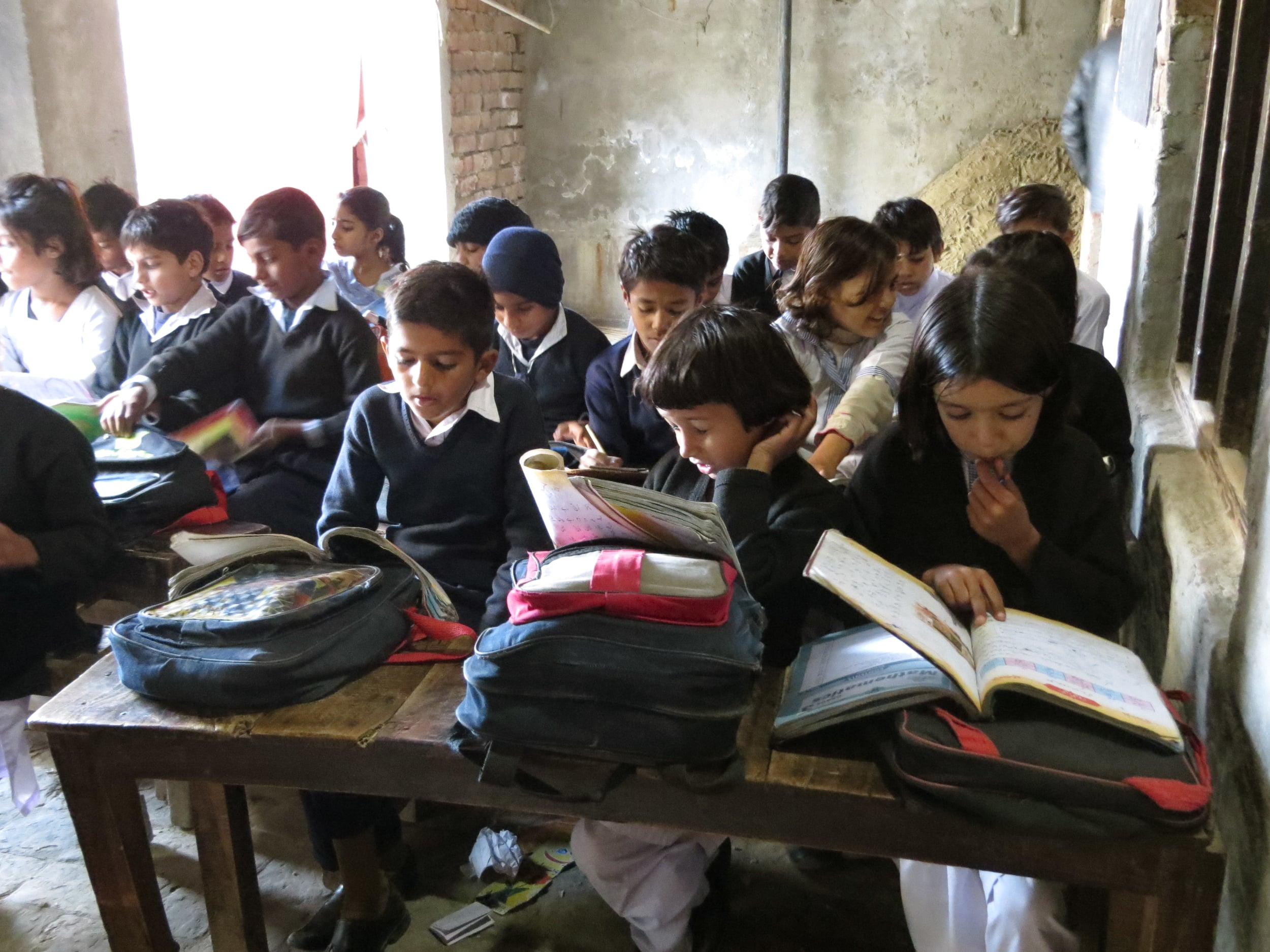 STUDENTS LISTEN AND REPEAT AS THEIR TEACHER READS ALOUD FROM A TEXTBOOK AT A SCHOOL OUTSIDE OF FAISALABAD, PAKISTAN. PHOTO BY BEENISH AHMED.