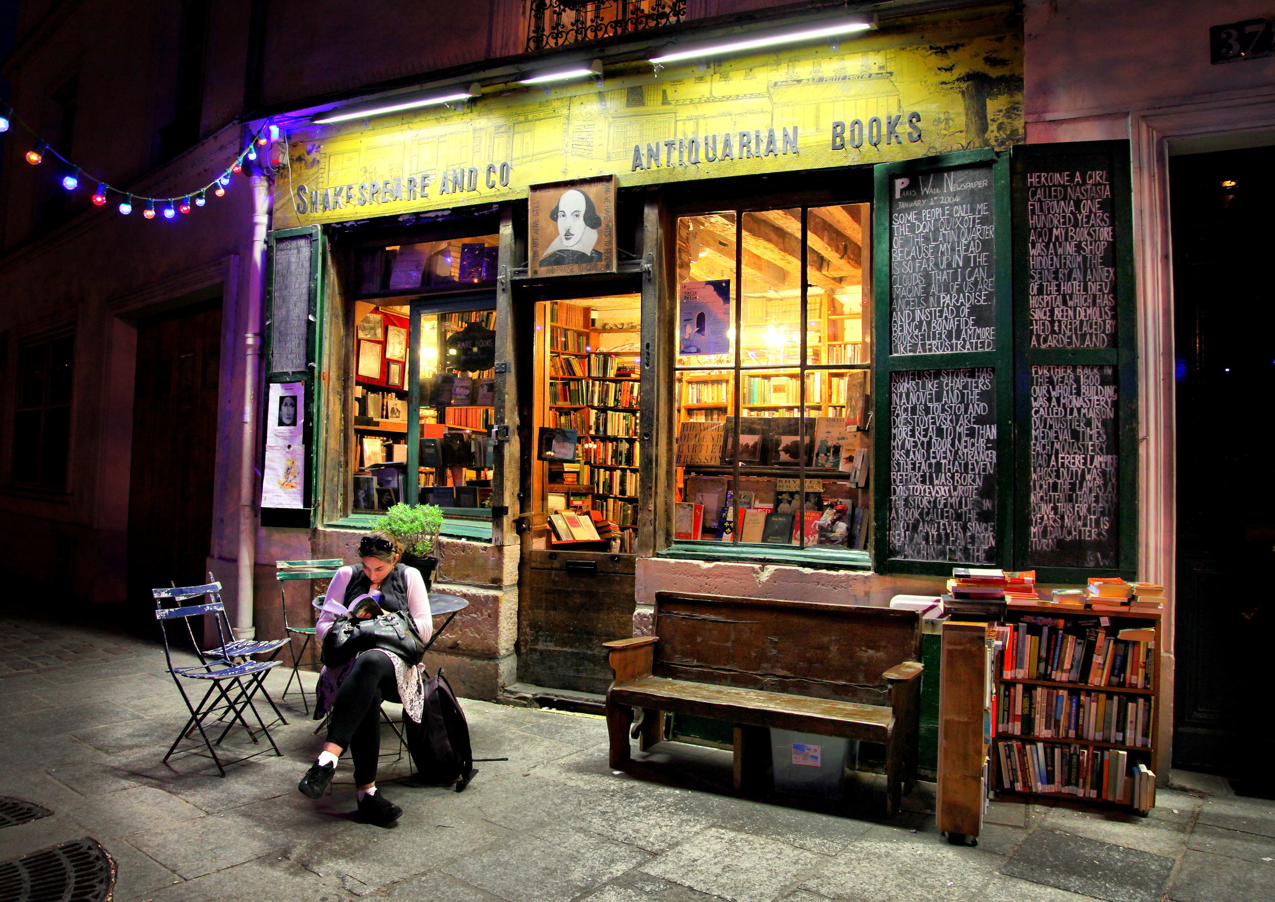 A woman reads outside of the iconic Paris bookstore, Shakespeare and Co. Photo by Christine Zenino via Wikimedia Commons.