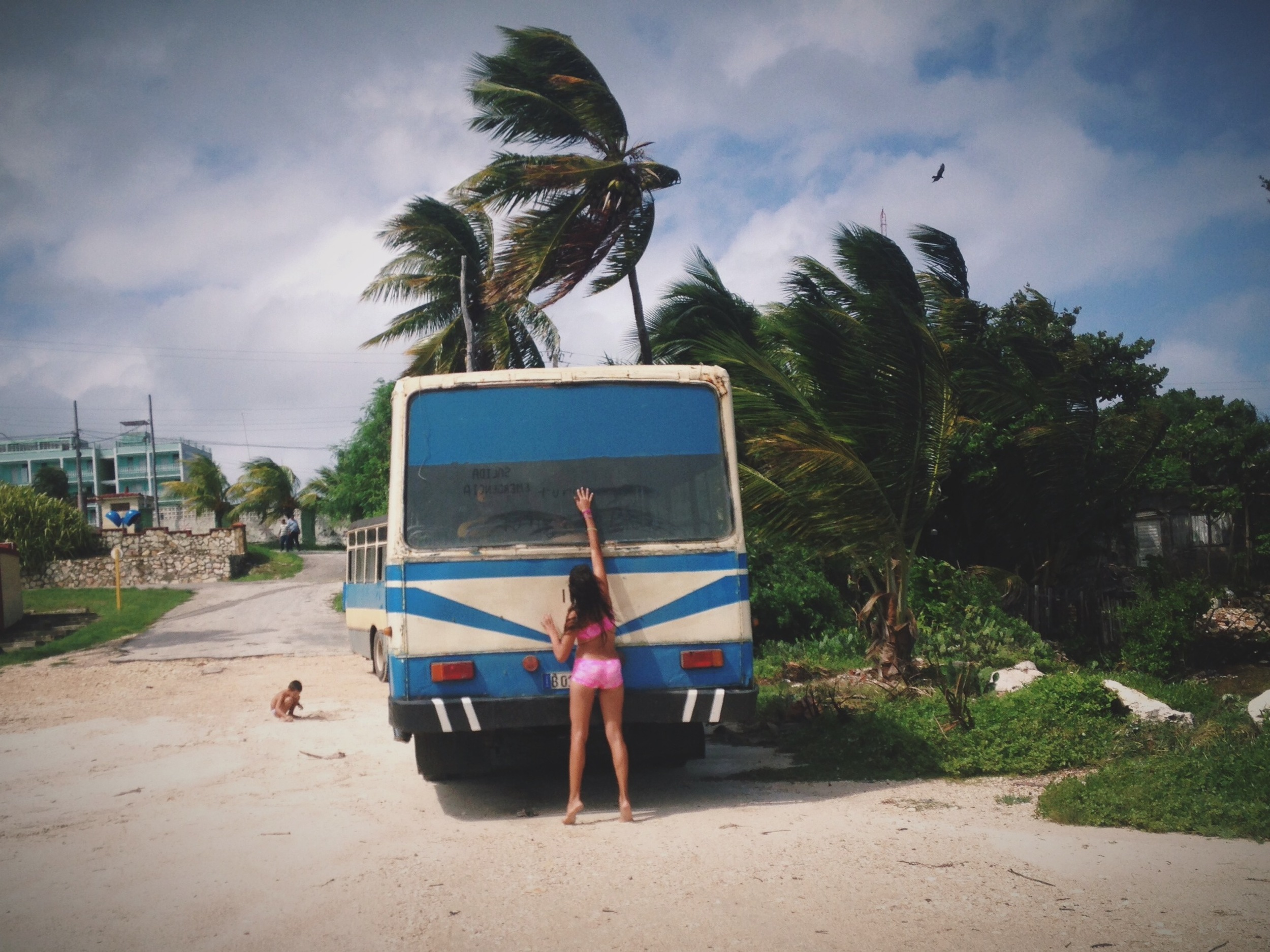 a girl writes in the dust on the back of a van in havana.photo credit: meghan dhaliwal for the alignist.