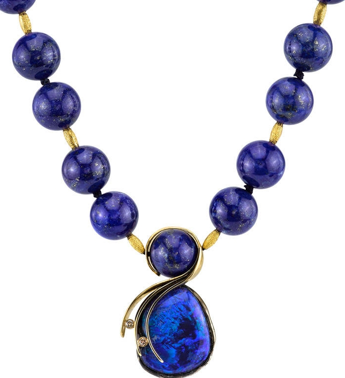 A Lightning Ridge Opal hangs from an 18 Karat Yellow Gold chain studded with natural Lapis Lazuli beads. The pendant, accented with 20 Karat Yellow Gold and White Diamonds, is a work of art within itself.
