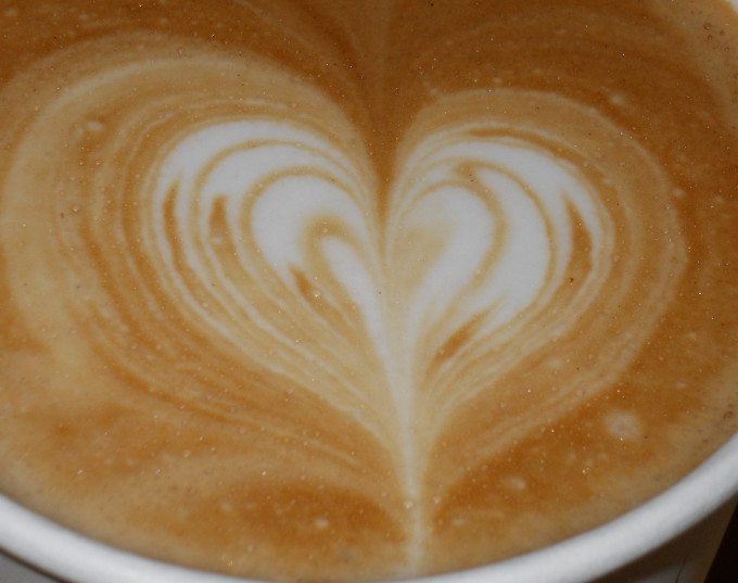 Pouring a layered heart in a to-go cappuccino