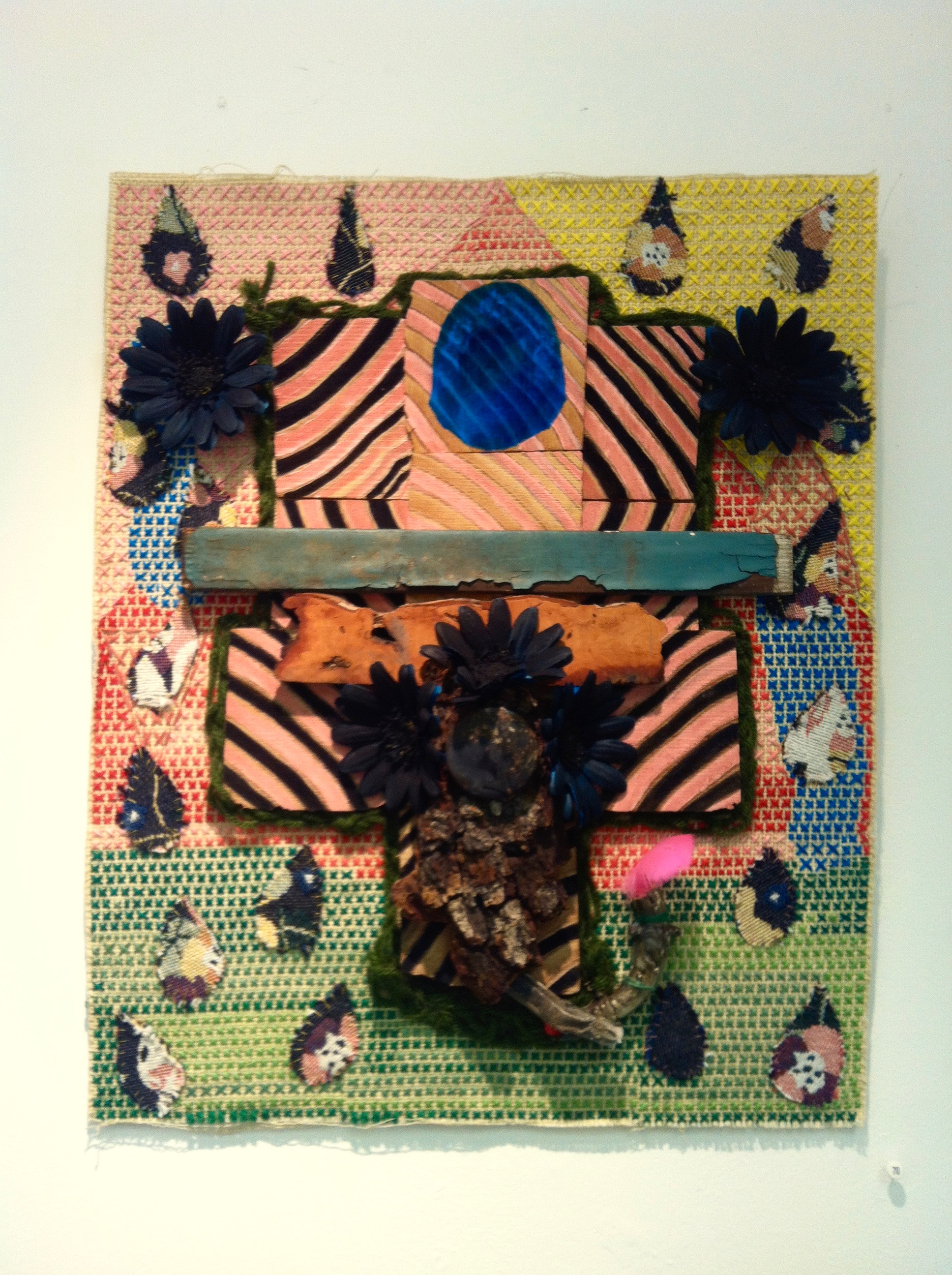 Heathcliff , needlepoint with fabric, found wood, paint, candelabra, nylon flowers, and feather, 12 x 16 inches