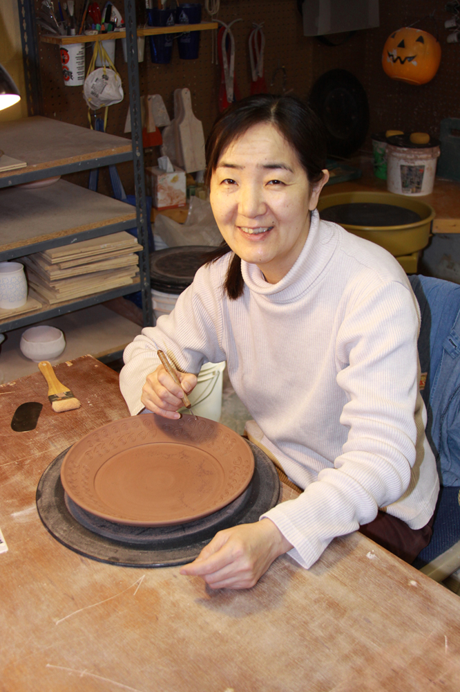 "Sumiko Takada  has been working with clay for over 15 years. She has studied in Japan with Yasunori Nishio and Jun Terada both in Komaki, Aichi and in the United States at Worthington Community Center and Columbus College of Art & Design.  Her recent exhibitions include ""Patterns in Clay: Two Approaches"" atCanton Museum of Art, Canton, OH, ""2016 Ohio State Fair Fine Arts Exhibition"" receiving Ohio Arts Council Award, Columbus, OH and ""Building"", a group exhibition at Fitton Center for the Arts, Hamilton, OH.  Sumiko creates her functional work with stoneware that is fired to cone 5 in oxidation. Her inlaid pieces are painstakingly crafted by hand: first carving the designs on the ware, then filling them with colored slip, and finally cleaning up the excess slips. She also uses slip decorations and various glazes of her own formula in her work."