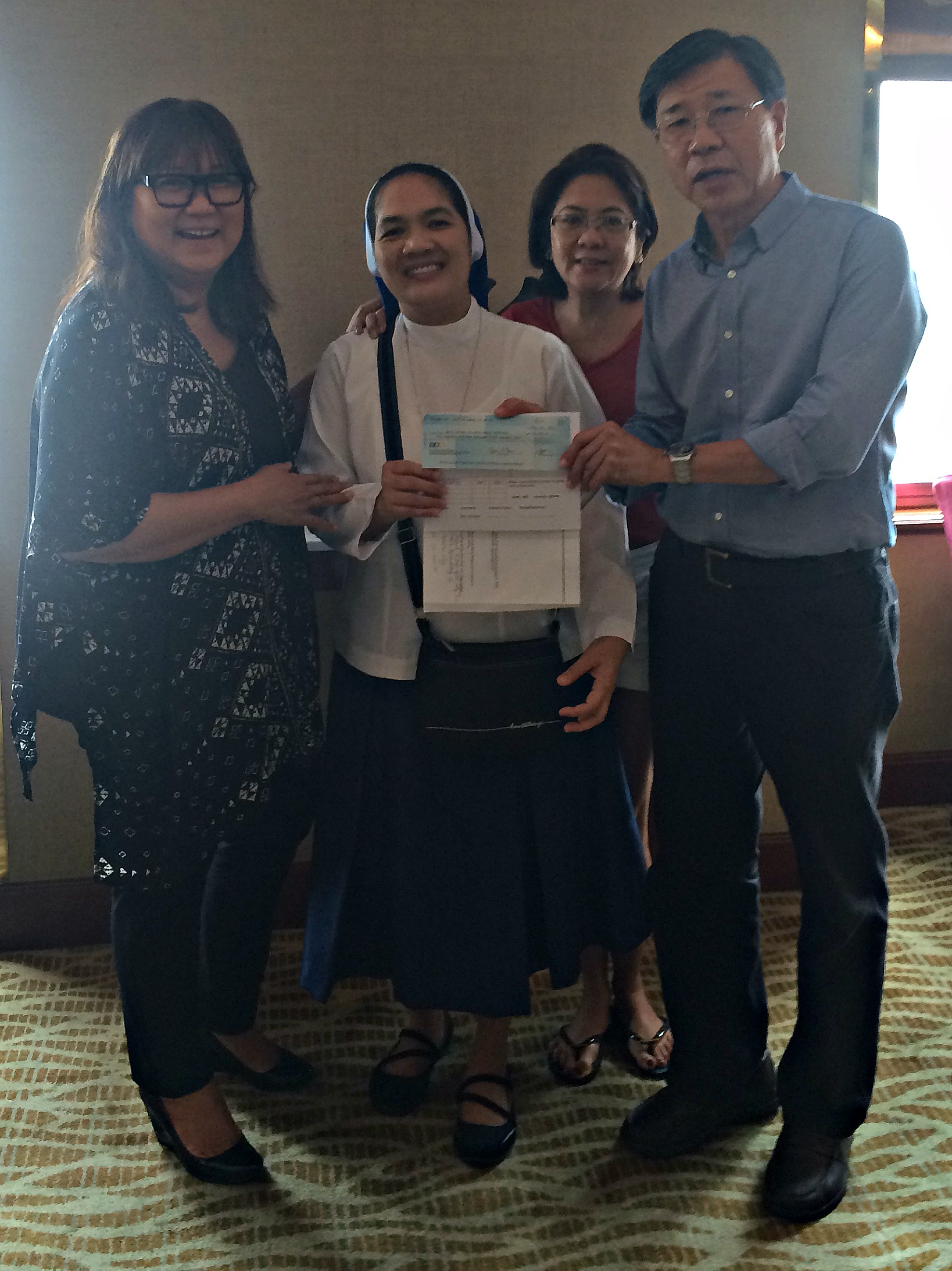 Sister Sonia Marie Ubaldo, Treasurer of Holy Infant College of Tacloban City, receiving the donation check ($5,000 = P215,500.00) for the Holy Infant College of Tacloban City, Inc. for the   Balay Darangpanan - Mercy Center - as the Psychosocial Healing Center for Women, Girls and Children Survivors of Typhoon Yolanda   from Marily Mondejar, Filipina Women's Network Founder & CEO, Dr Bambi Lorica, Filipina Women's Network Board Member, Martin Gaw, Lamco International and Volunteer for Feed the Hungry Fil AM Inc, at the Makati Shangri-La Hotel, Philippines, October 15, 2014.