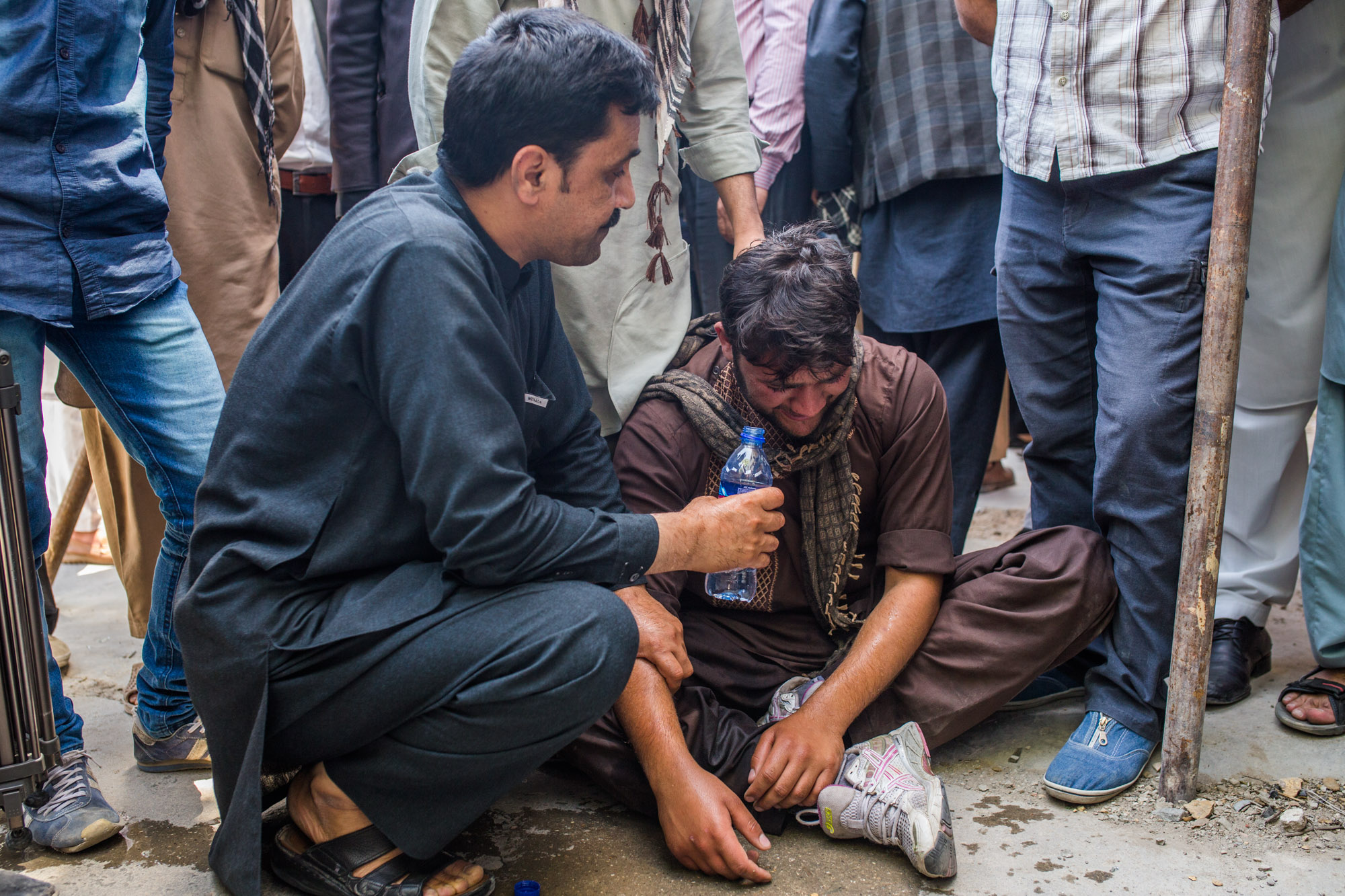 A young man is consoled after discovering that his brother was just killed in a massive suicide attack in downtown Kabul. May 31, 2017.