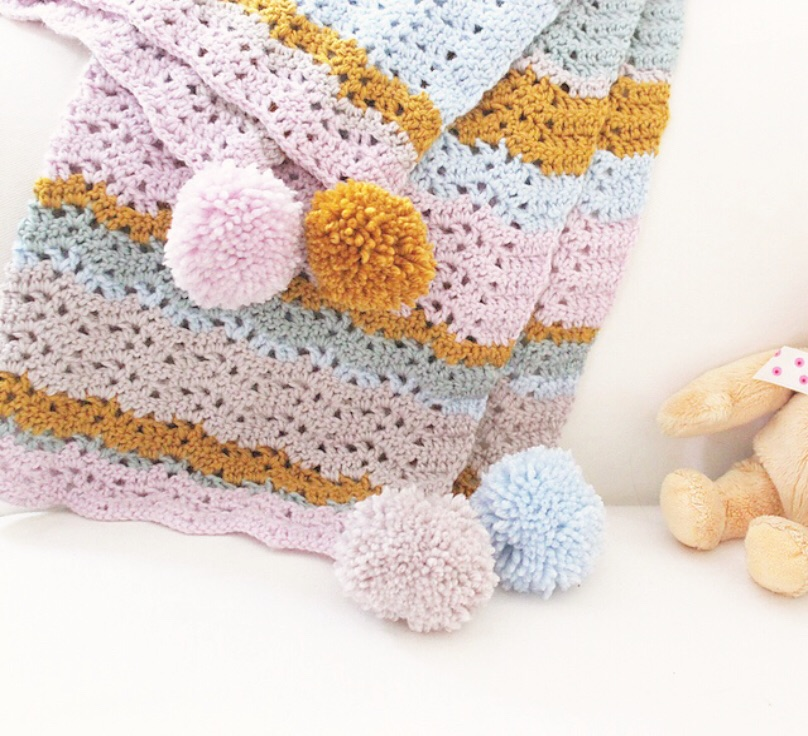 isla - The prettiest of baby blankets in muted, pastel colours. This openwork ripple blanket is easy to crochet and looks perfect finished off with pom poms. DK. Five colours. Easy/Intermediate. More details and pictures.