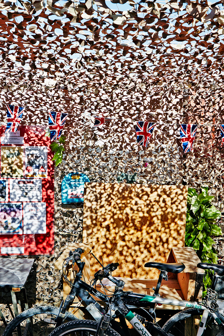 6 SHEET POSTER IN WIMBORNE   This is an image of one of the operations areas that is known as the Reverse Supply Chain,   photographed on the 29th April 2014.    This relates to the logging and packing away of equipment that is due to fly home.    Very often you find working areas covered by camouflage netting which in the harsh midday light produces an incredible mottled pattern of light and shade.