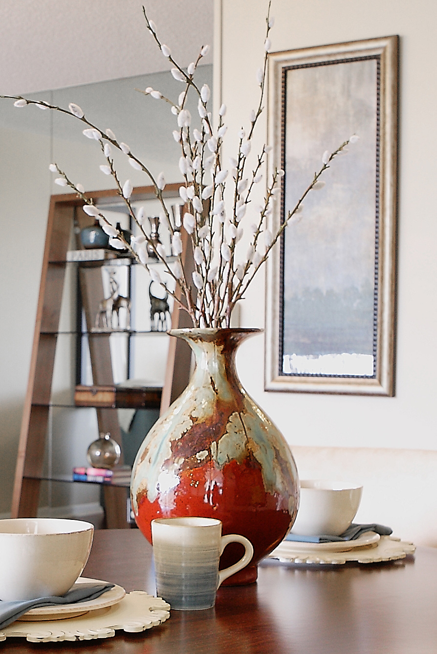 Detail view from home staging client project by Captiva Design; vase and pottery on table in open floorplan home
