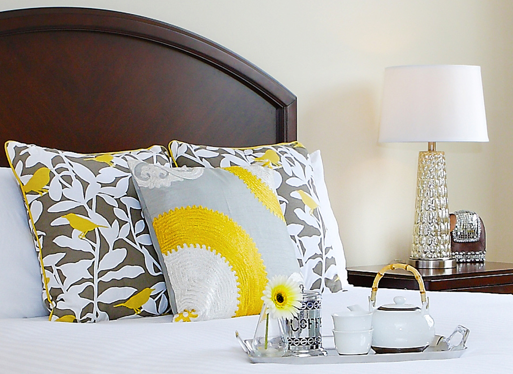 Captiva Design home staging services. Close up detail from bedroom featuring tea service on tray sitting on white bed with yellow and gray accent pillows, lamp in background with rich cherry headboard.