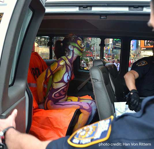 She was nude then she sued.  Zoe under arrest in Times Square for being part of body painting exhibition by .