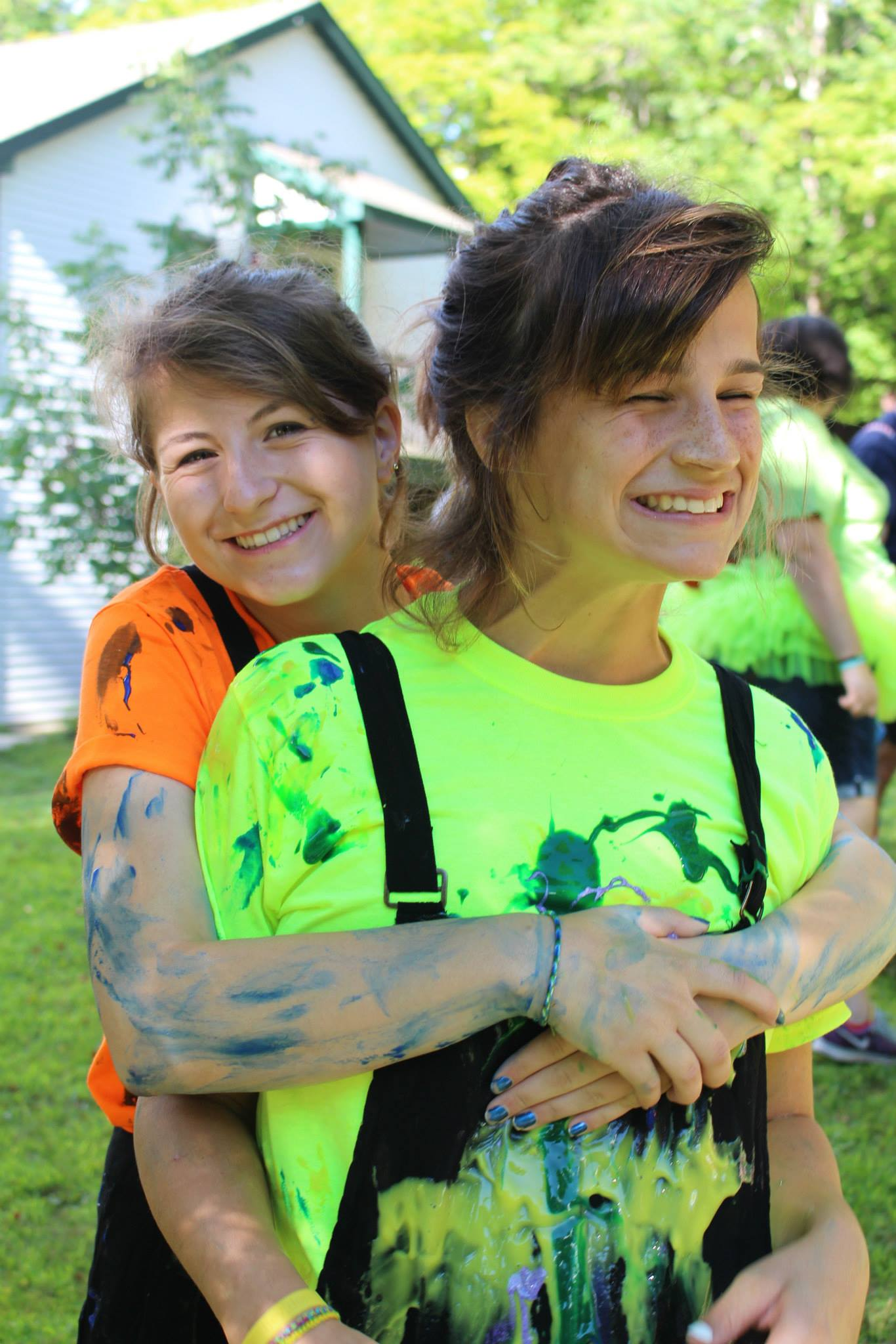 Coral (left) with camper Ellen, smiling after allowing the other campers to decorate their costumes with paint-filled balloons