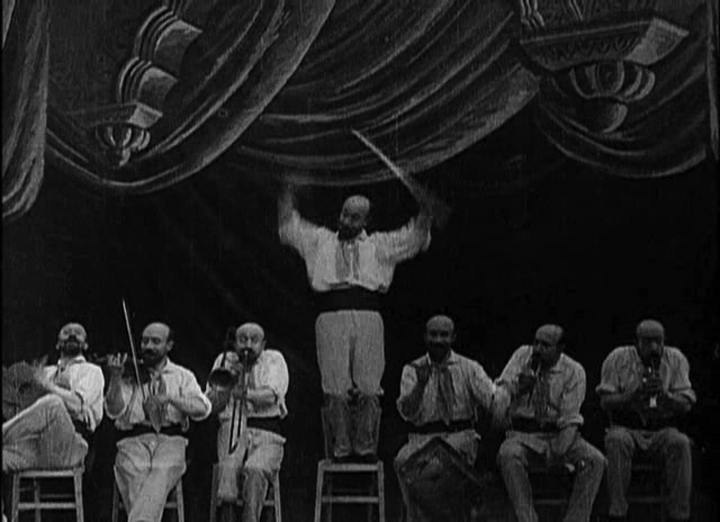 Multiple copies of Georges Méliès in the 1900 film,  The One-Man Band  •  Wikimedia Commons