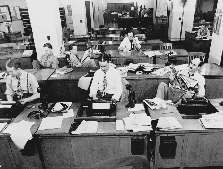 New York, New York. Newsroom of the New York Times newspaper. Reporters and rewrite men writing stories, and waiting to be sent out. Rewrite man in background gets the story on the phone from reporter outside. September 1942. •  Wikimedia Commons