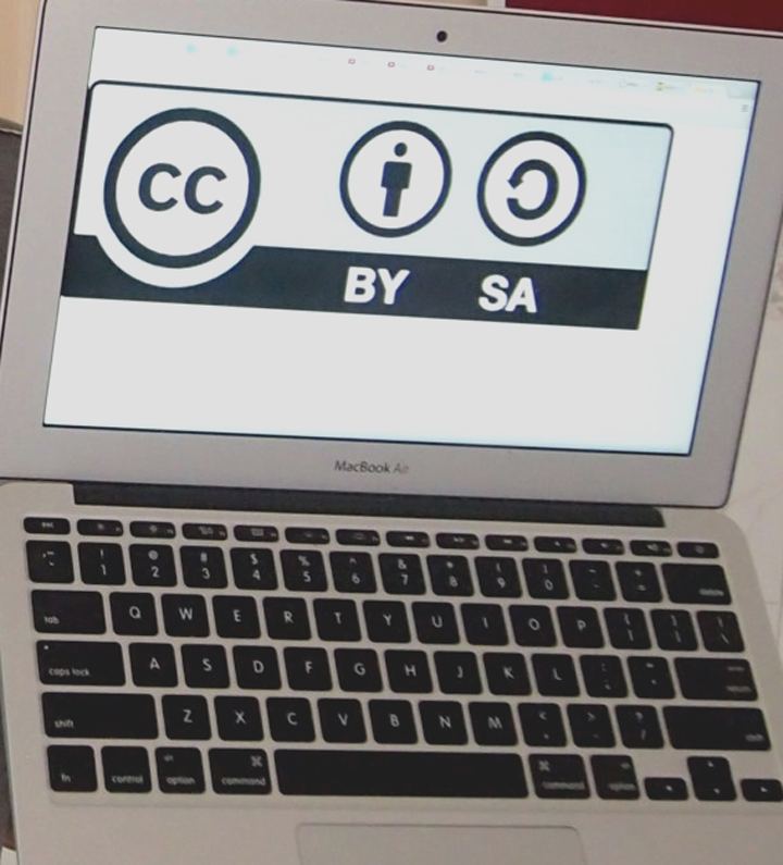Pagna holding a page of Khmer script describing releasing rights for use in Wikipedia commons, and screen showing CC license logo, from workshop at Building Community Voices in Phnom Penh, Cambodia. (IMAGE CROPPED) •  Wikimedia Commons