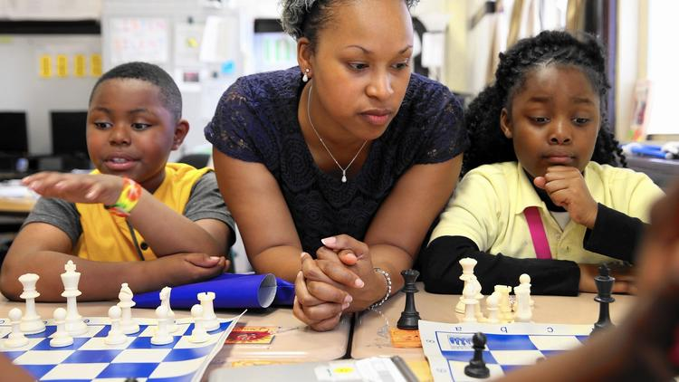 Candice Usher, center, a teacher at Fuller School of Excellence in Chicago, shows students Charleston Rice, left, and Nic'Kita Williams, right, how to play chess. (Terrence Antonio James / Chicago Tribune) Copyright © 2017,  Chicago Tribune