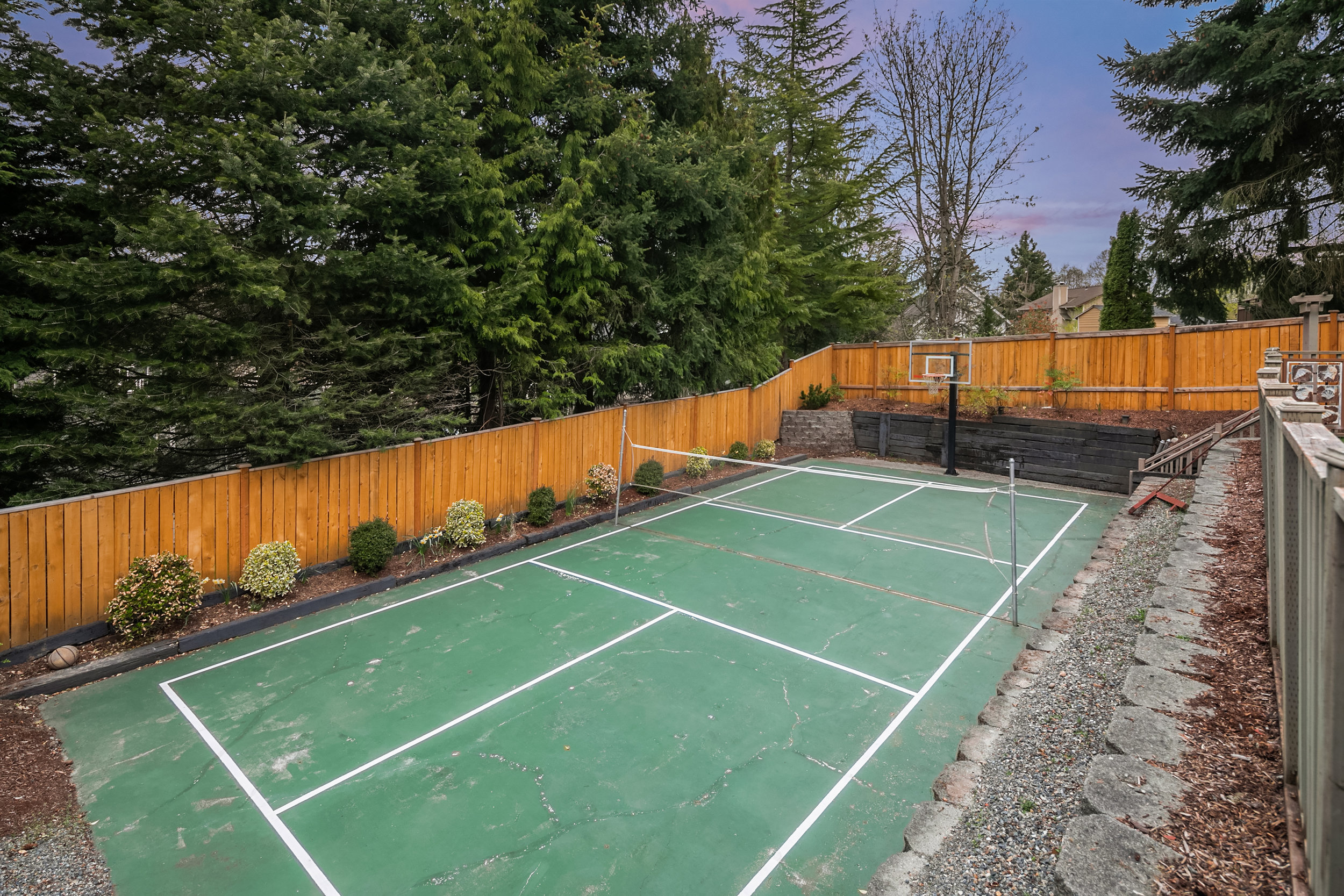 An expansive sports court, landscaped and ready for a game of pickleball!