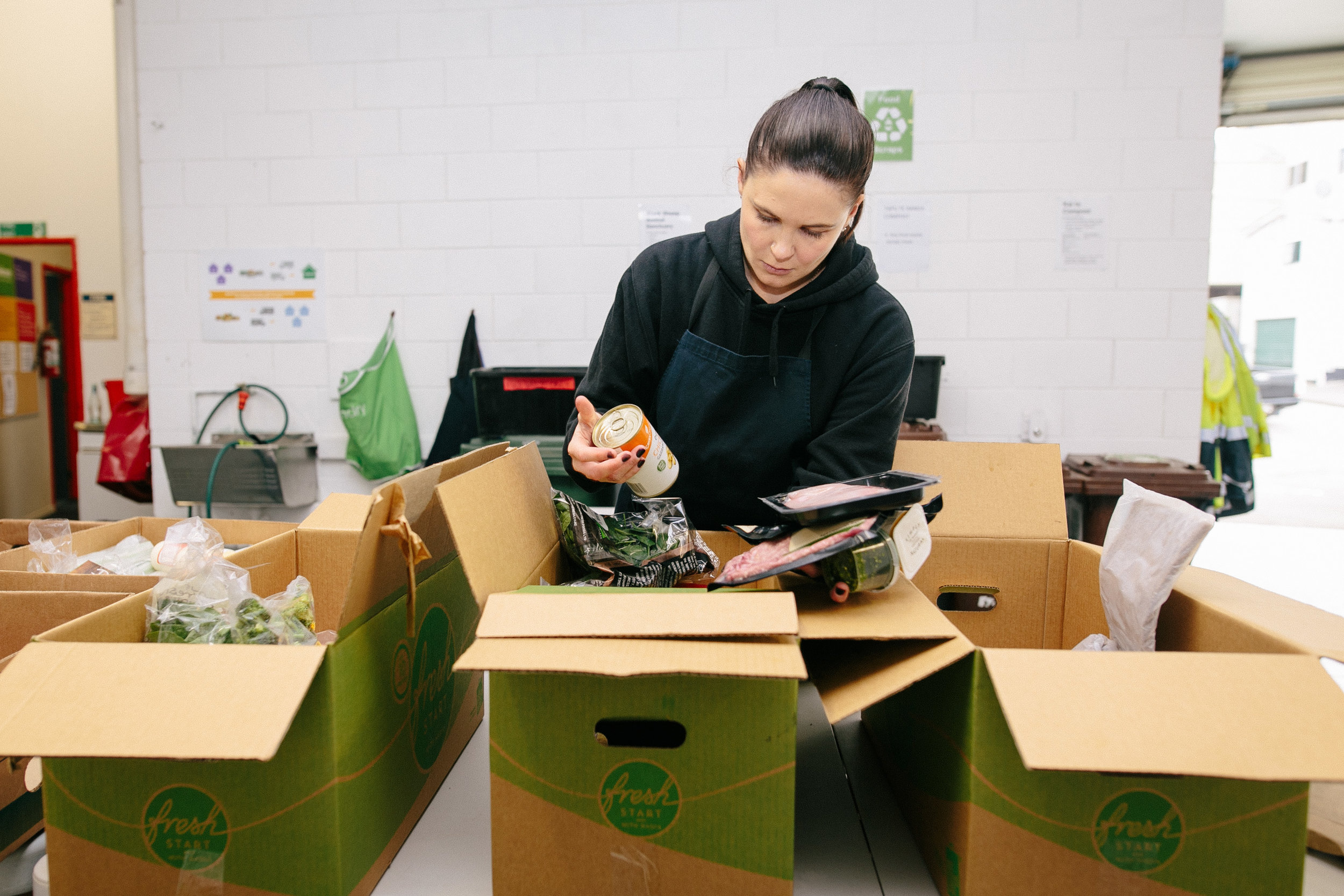 Hayley Osborne checks that a boxful of donated food is still in tip-top condition – anything too far past its peak is given to an animal rescue charity or turned into compost.