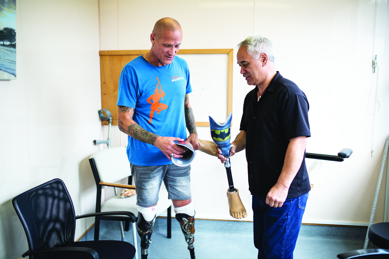 Ken presents new swimming legs to Shane at NZALS in Wellington. Shane wanted superhero designs for his grandchildren.