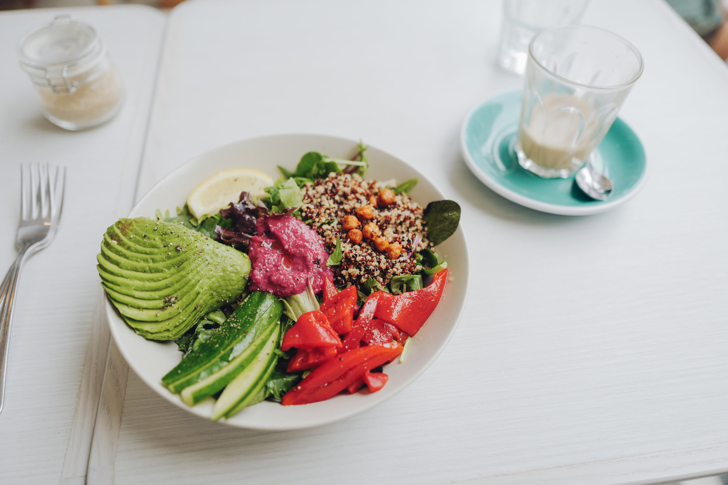 (Vegan)  Quinoa Bowl , with rockets, avocado, cucumber, roasted chickpeas, roasted peppers, beetroot hummus and Lemon. Oat Milk Latte.
