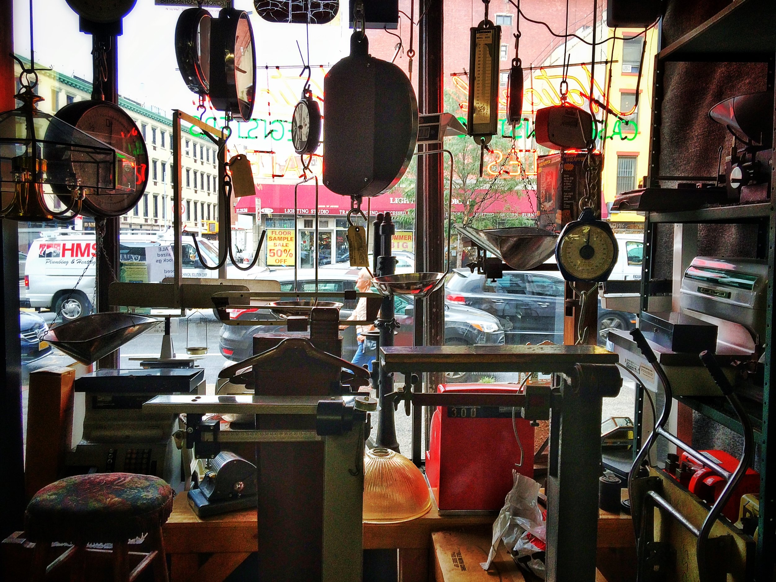 The shop's view of the Bowery through various antique scales and equipment for sale. Photo credit P. Peterson