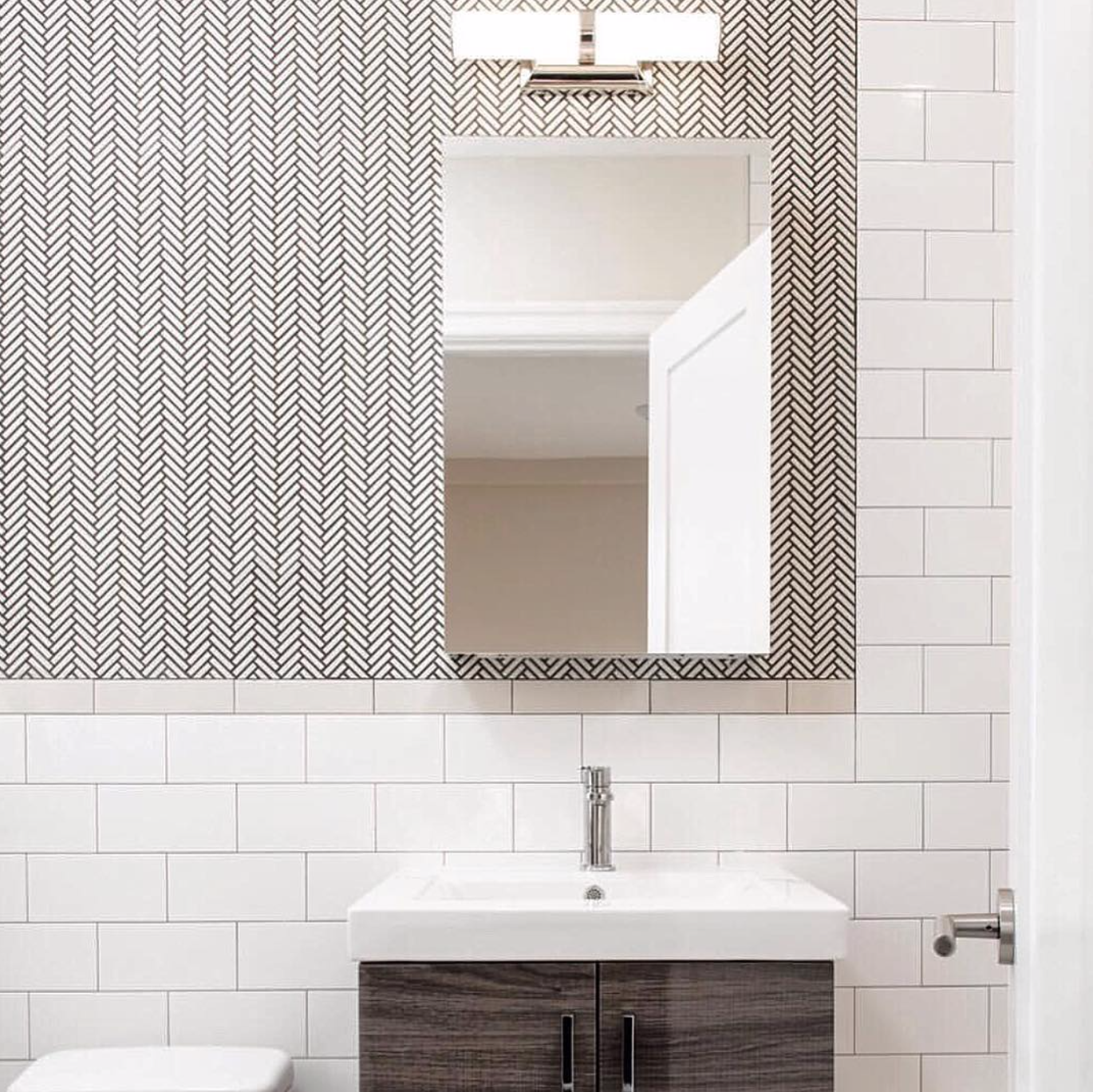 Bold herringbone tile and sleek storage solutions give this New York City bathroom a clean and modern aesthetic. Design by  @perianth_buymyeye ; photo by  @njohnstonphotography