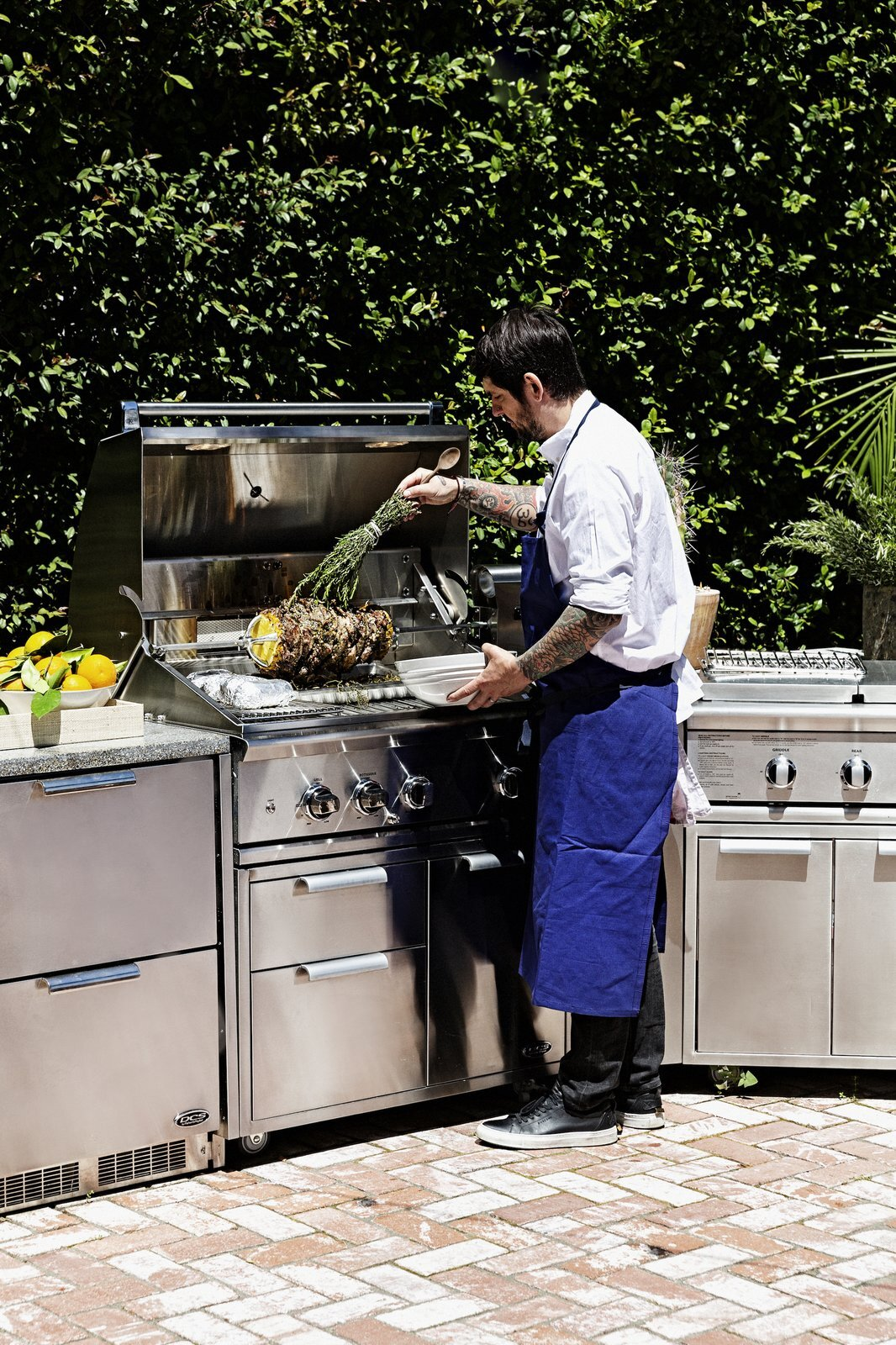 Chef Ludo preparing lamb shawarma on the grill's rotisserie—which can hold up to 50 pounds of meat—while roasting vegetables on the grills other surfaces.