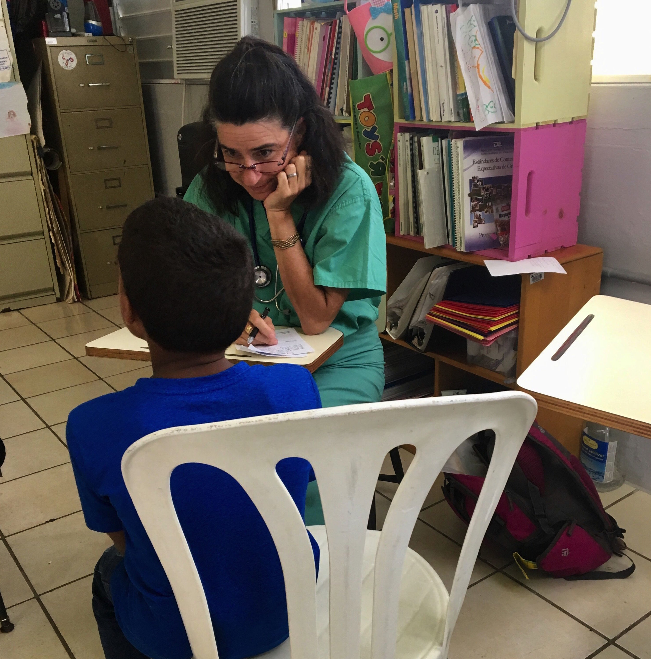 IMR volunteer, Angela Baumeister, RPAC, listens intently to her young patient