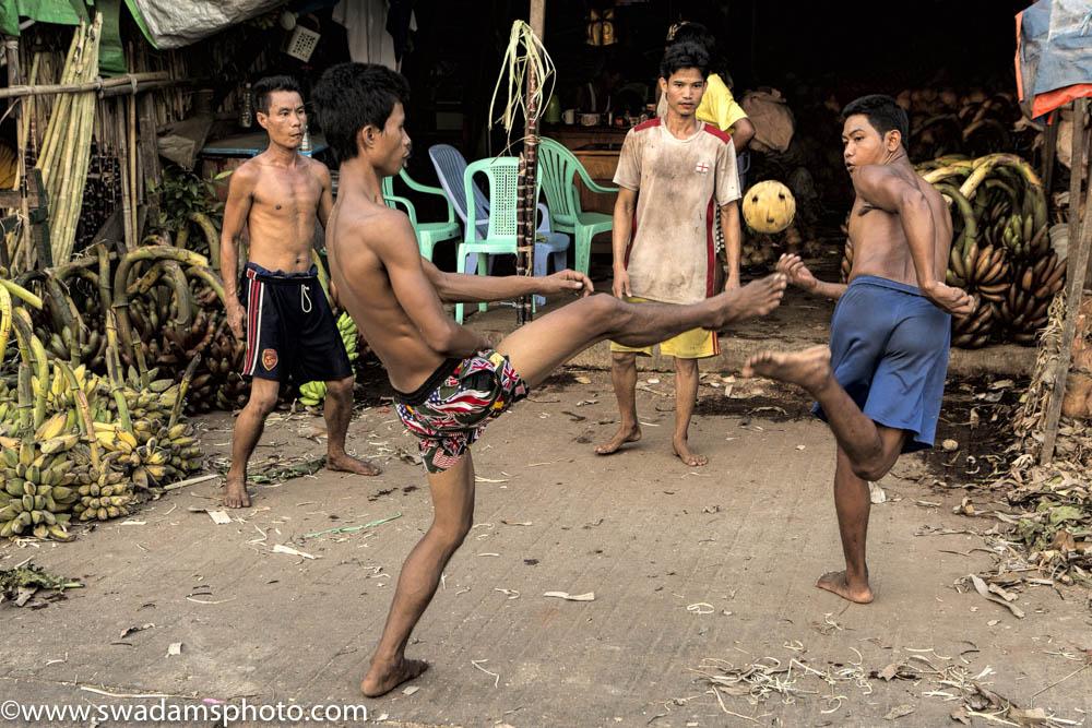 Young men take a break after unloading bananas to play chinlone, a popular Myanmar game similar to hackysac.