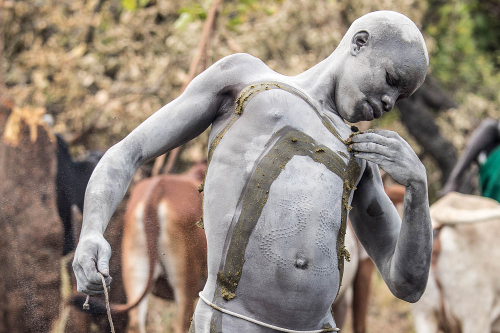 The Suri may also mark their bodies with clay or in this case fresh cow manure. Note the body scars.