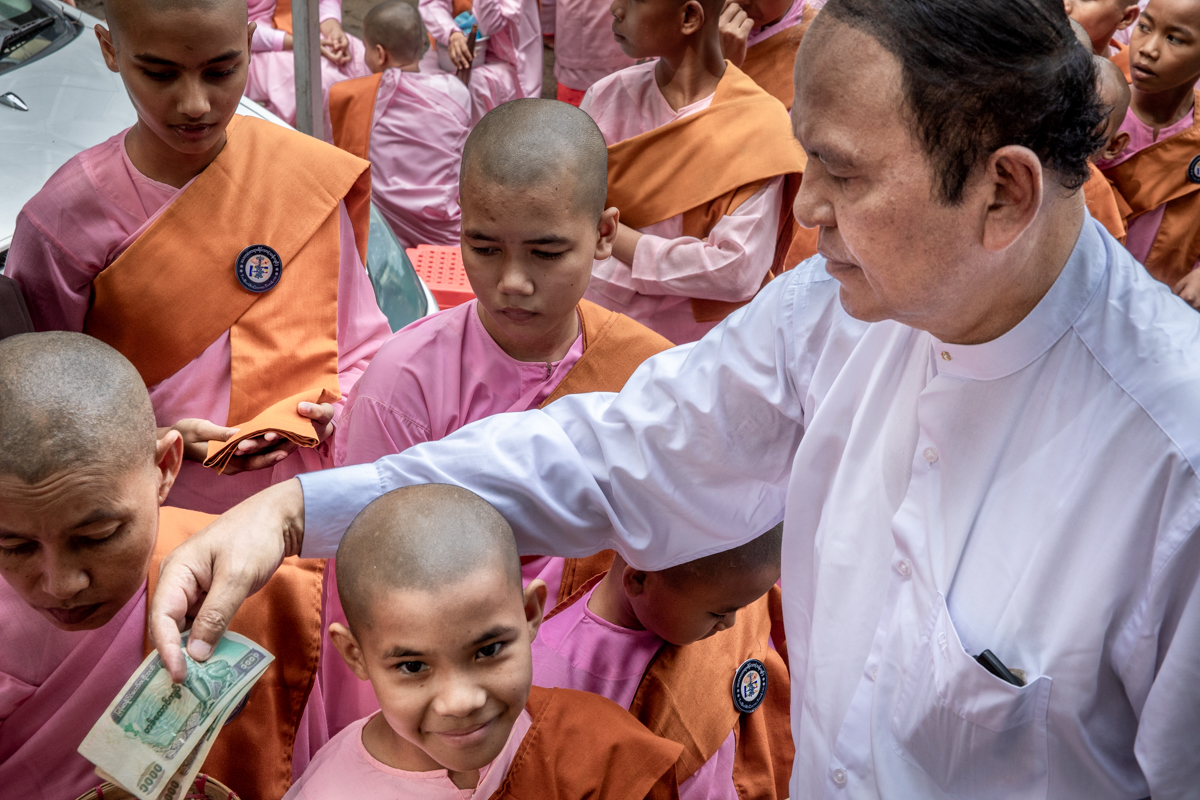 U Aung Than Sein distributing donations to the nuns. He is now assisted by his extended family so that the large number of small bills can be efficiently distributed.