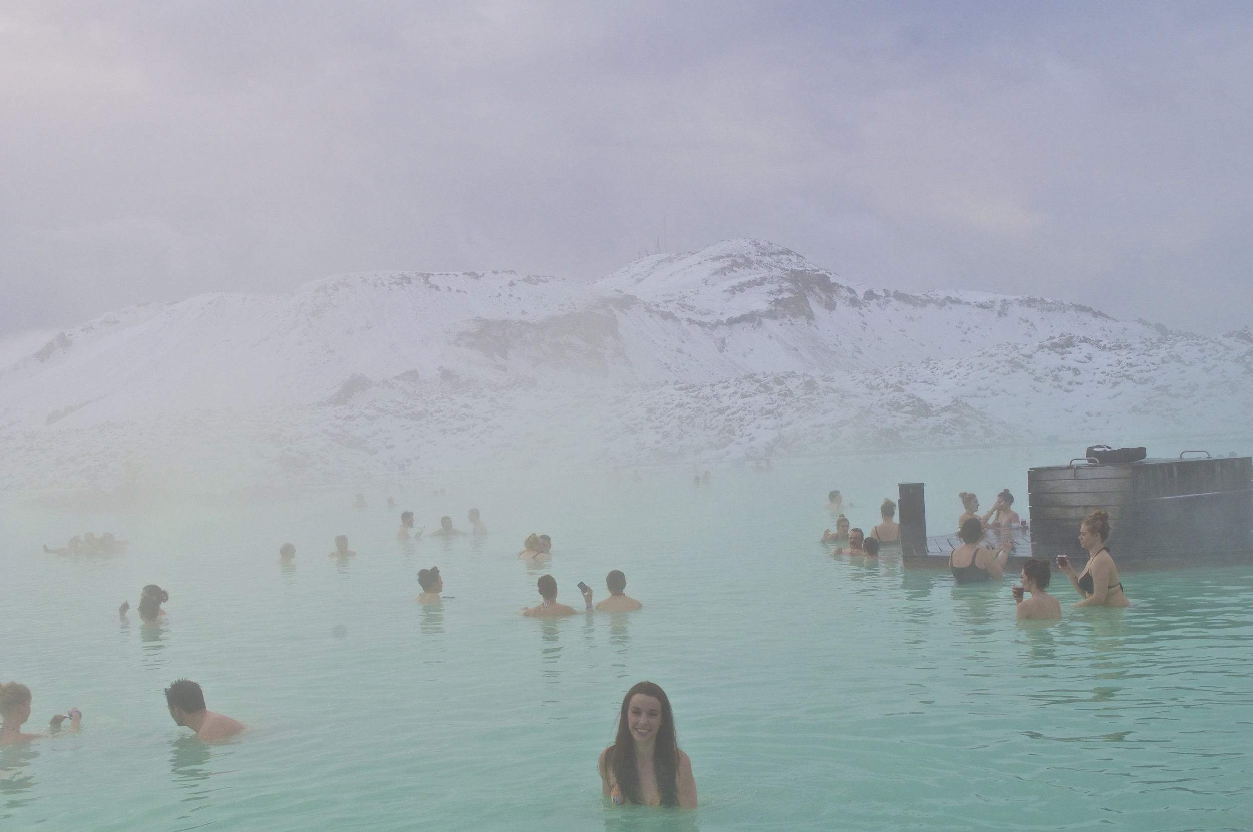 The blue lagoon is surrounded by lava fields covered in freshly fallen snow.