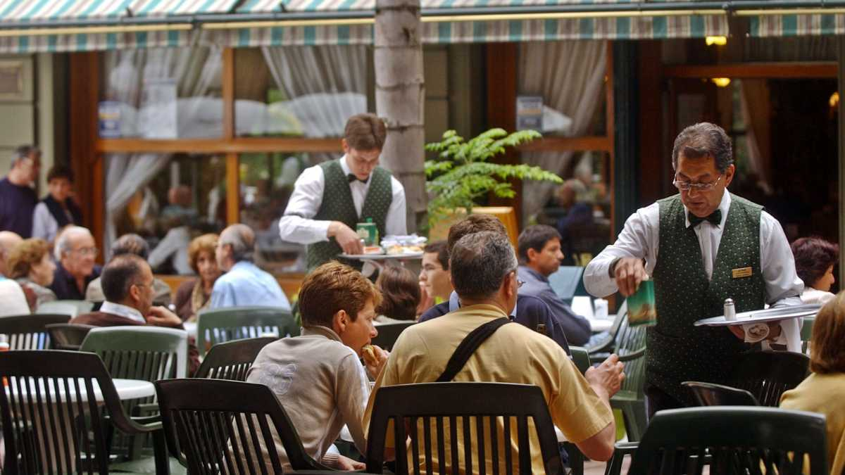 Waiters serve patrons dining in an outdoor cafe.