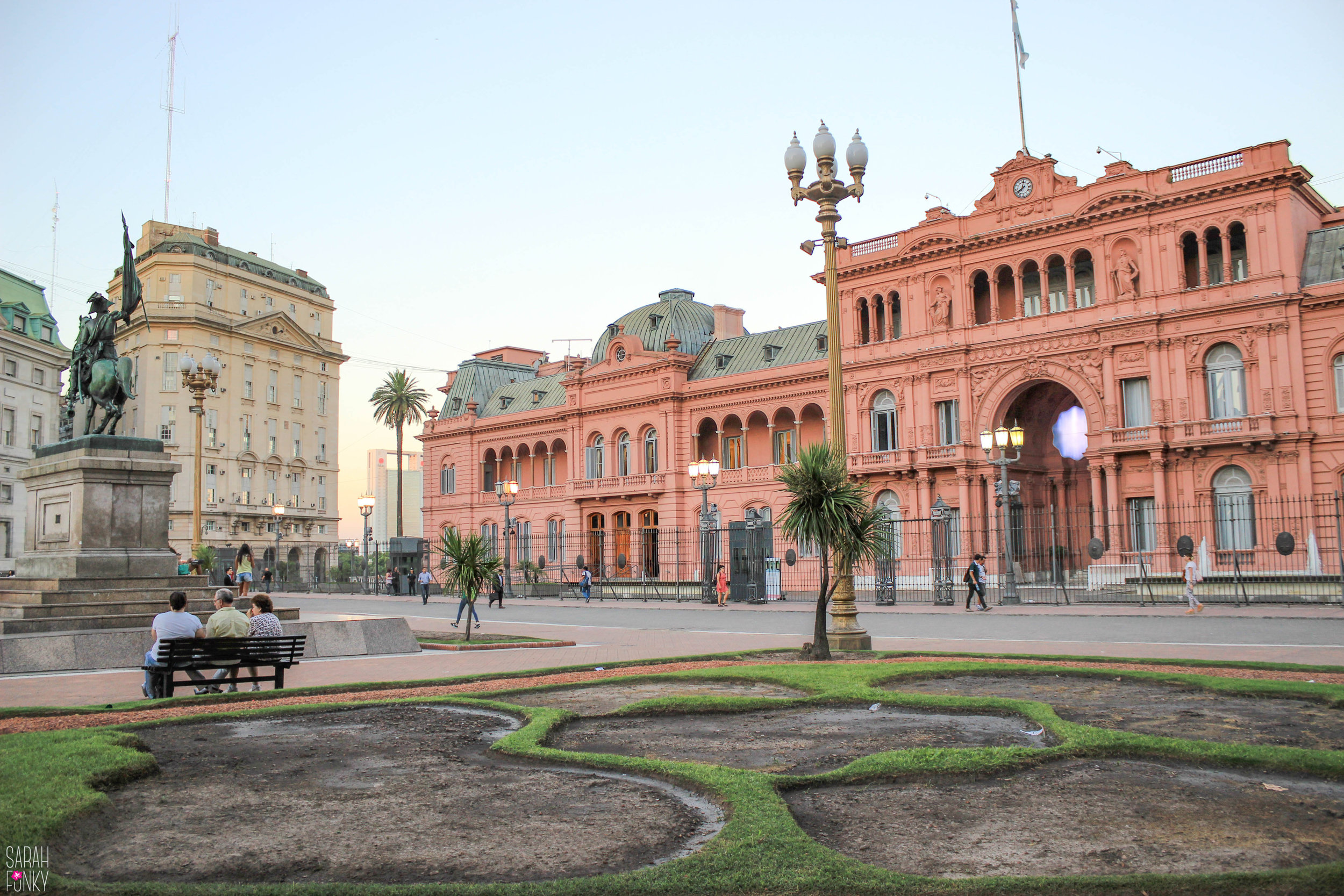 Portenos relax on a bench in the plaza outside of the Casa Rosada