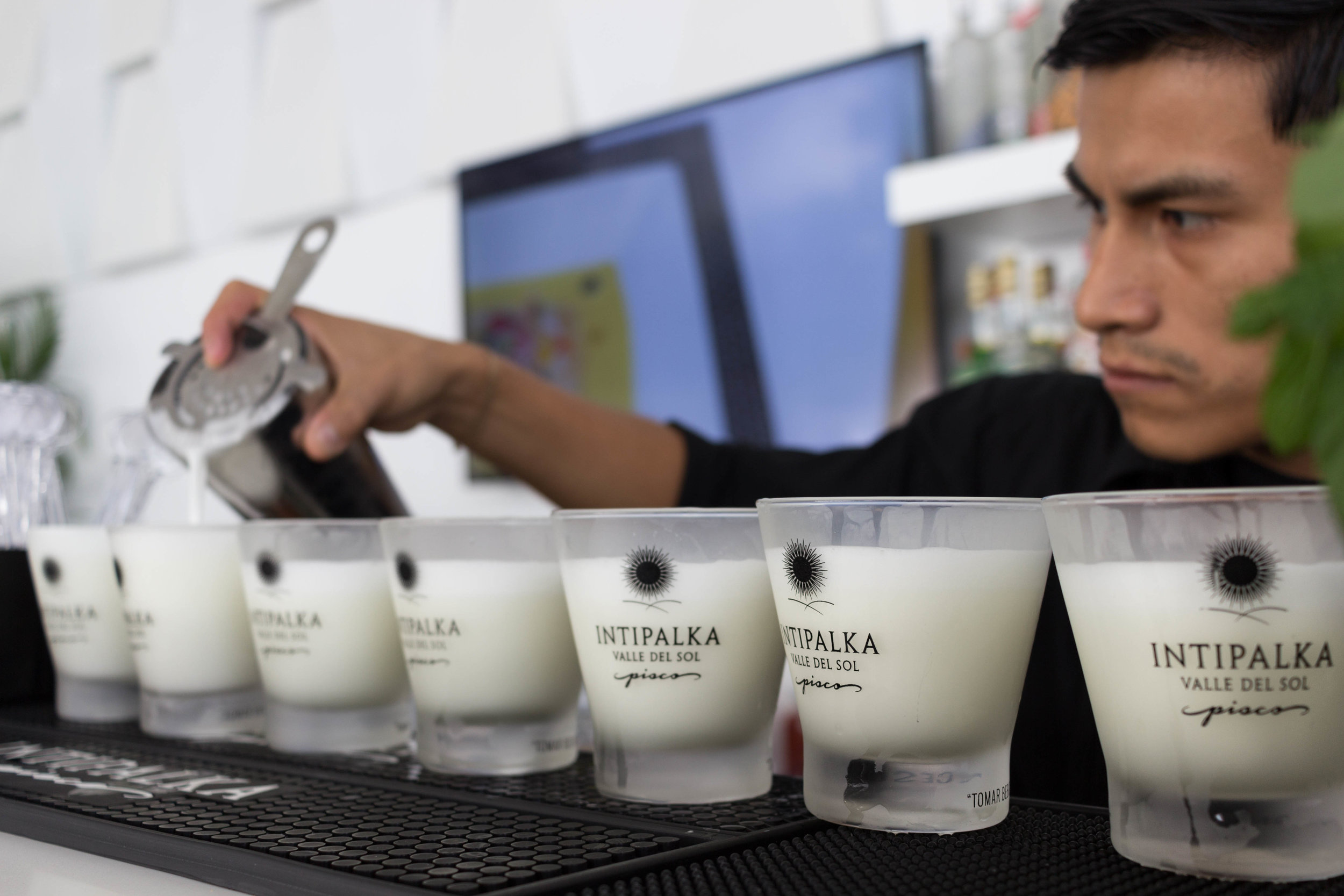 A bartender carefully pours Pisco Sour into frosted glasses.