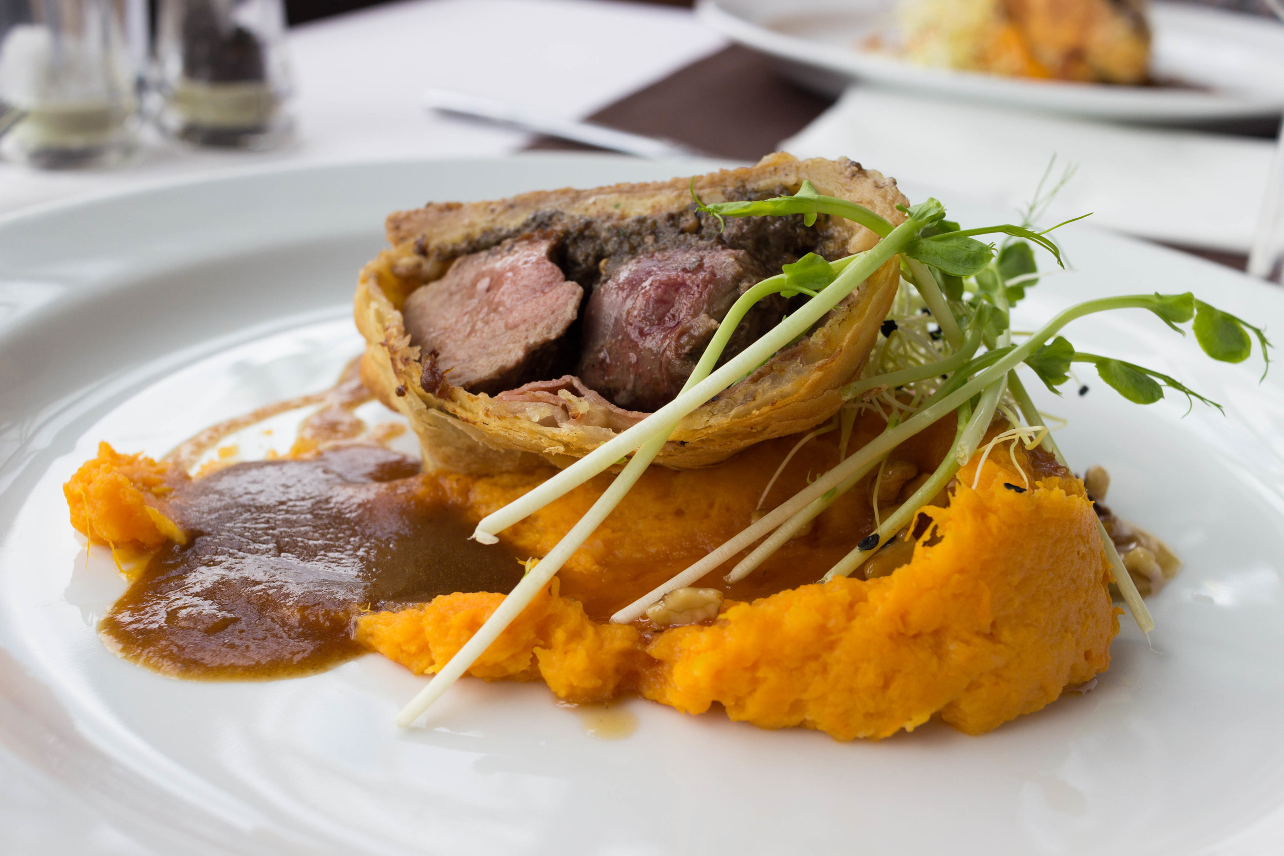 Wellington deer loin, stuffed mushrooms with herbs, wrapped in dry cured ham, sweet potatoes with walnut syrup and wine sauce