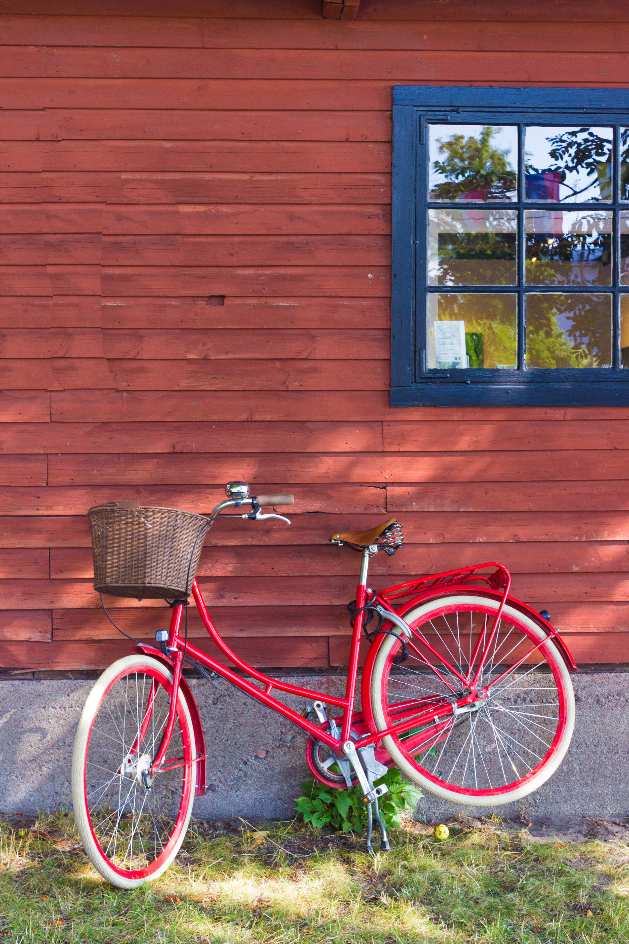 A bike rests against a traditional red house on one of the islands in Sweden's archipelago