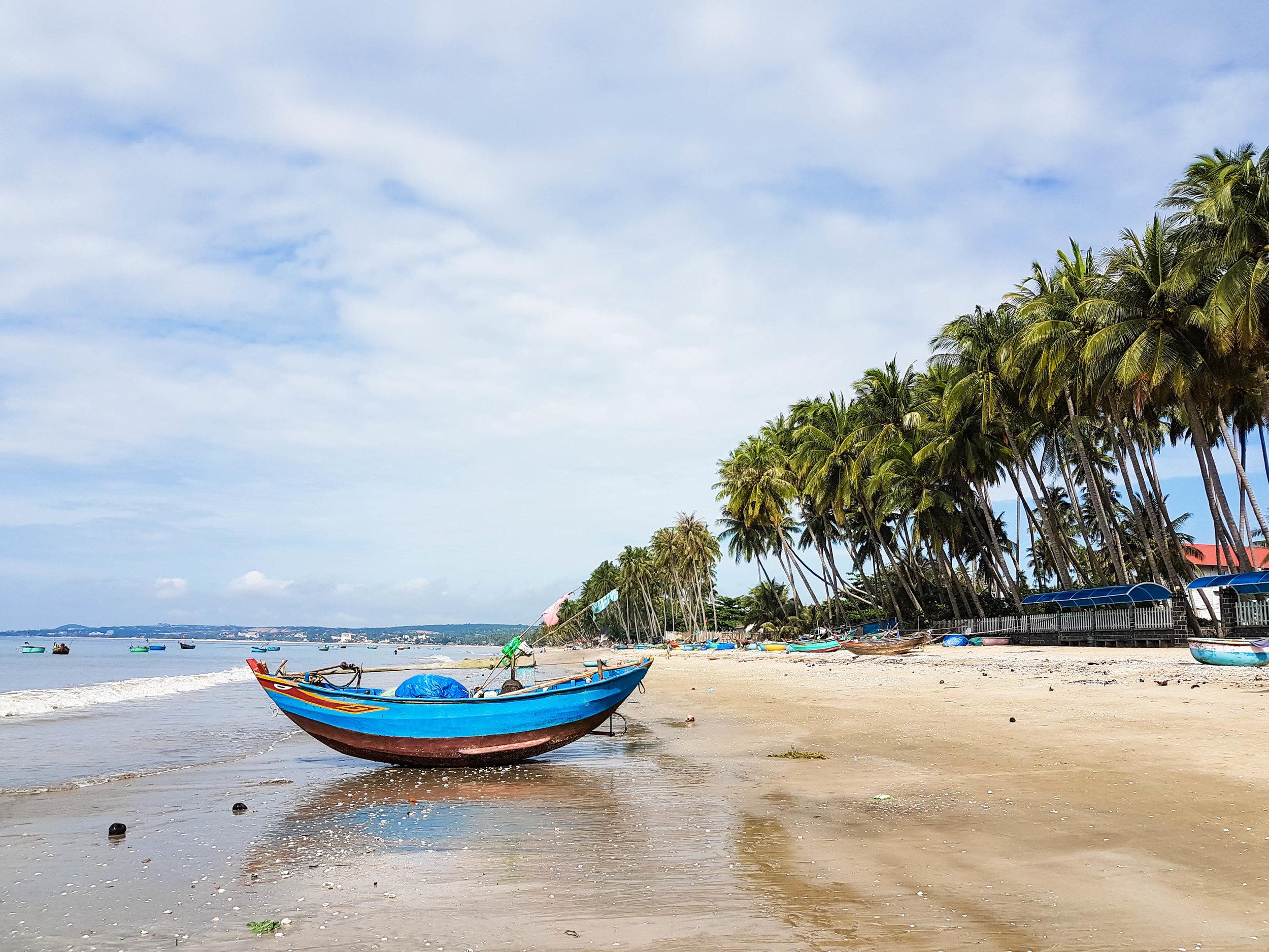 A fisherman's boat lies on the sandy beach of Mui Ne