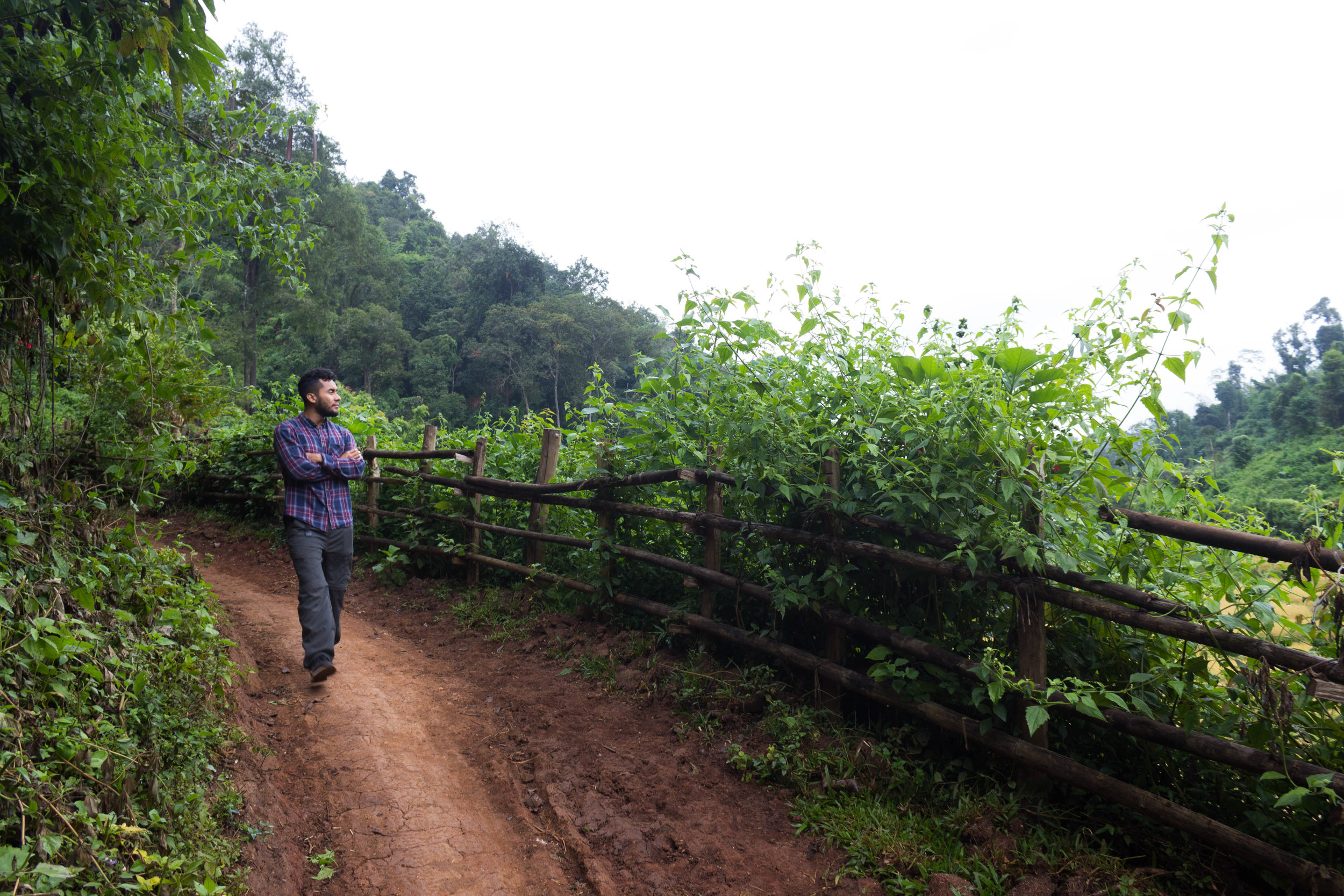 Walking along the red dirt road of the Karen village