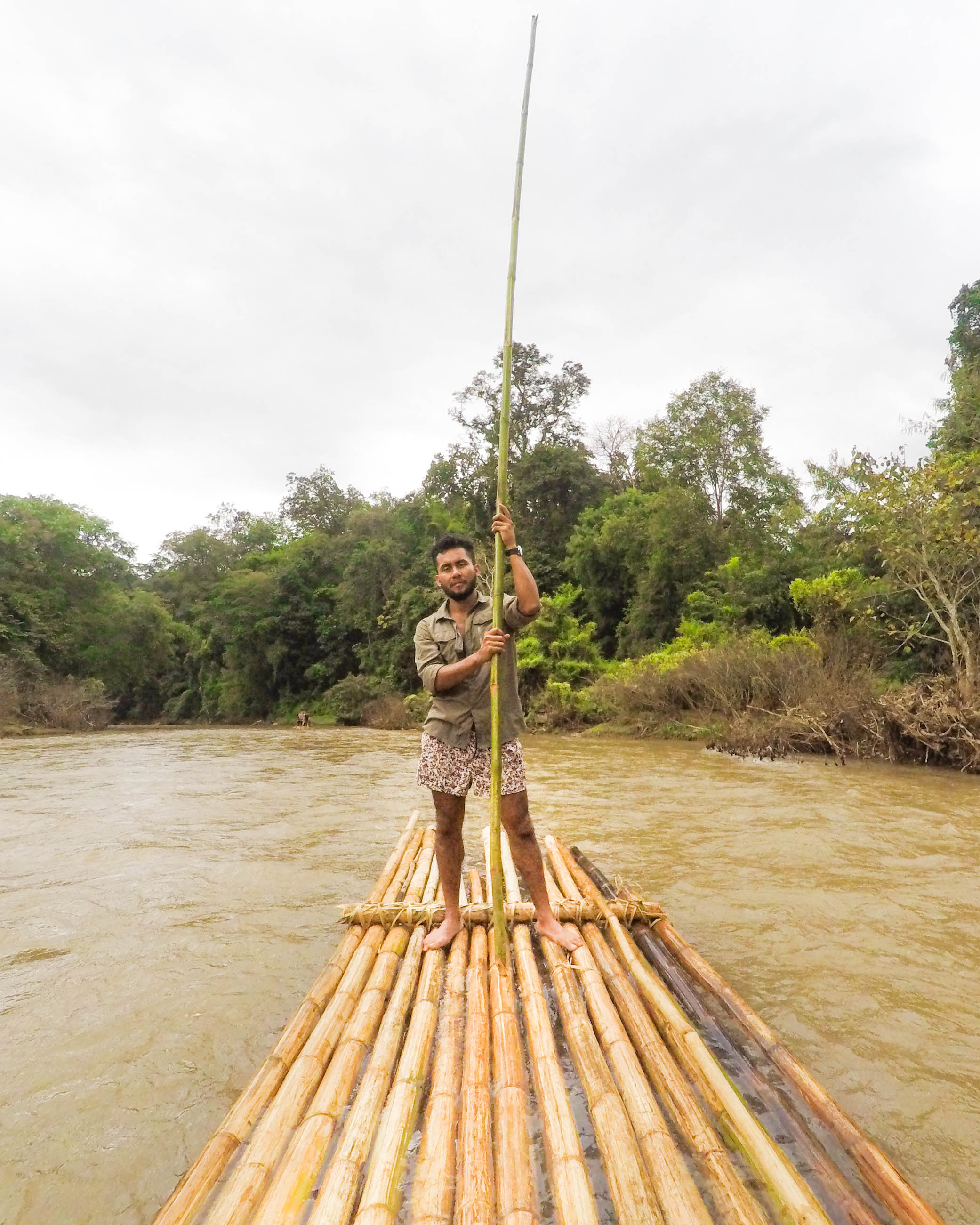 Luis brings up the back steering of the bamboo raft with a large stick