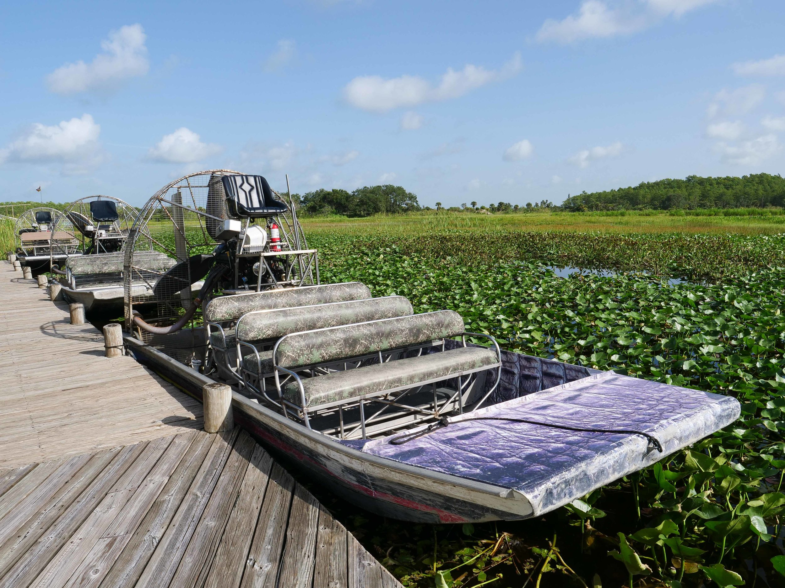 An Airboat is docked waiting for passenger's to board.