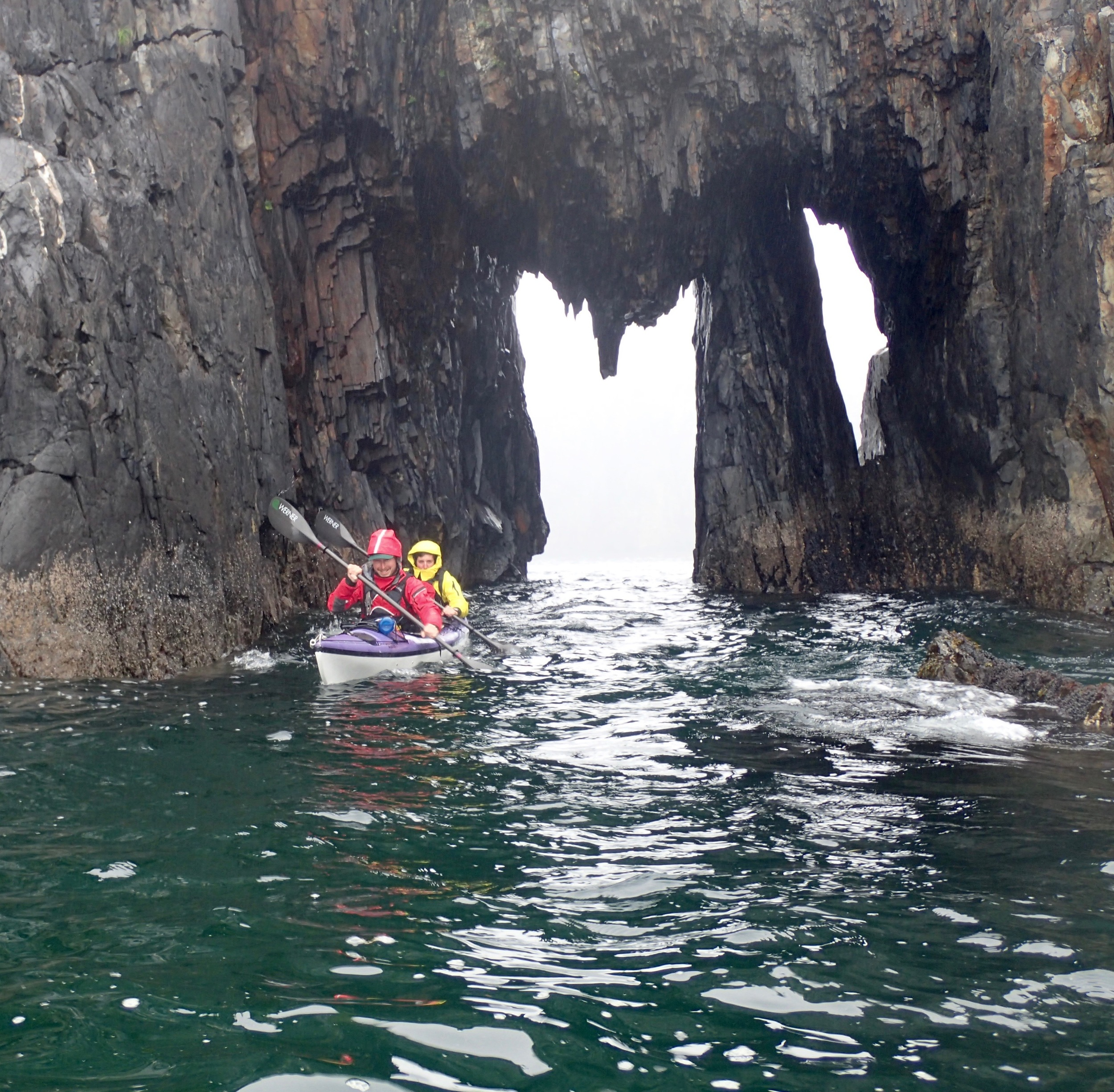Guides Andrew and Kelly (K2) paddling through the sea arch at Holgate Head at the end of the day.