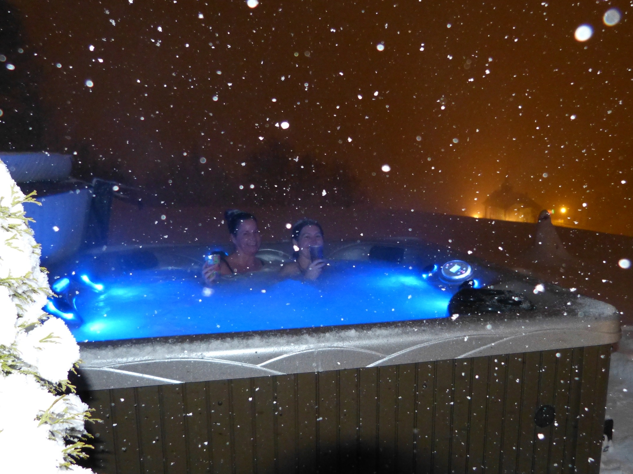 night time hot tub with a snowy view of the old church